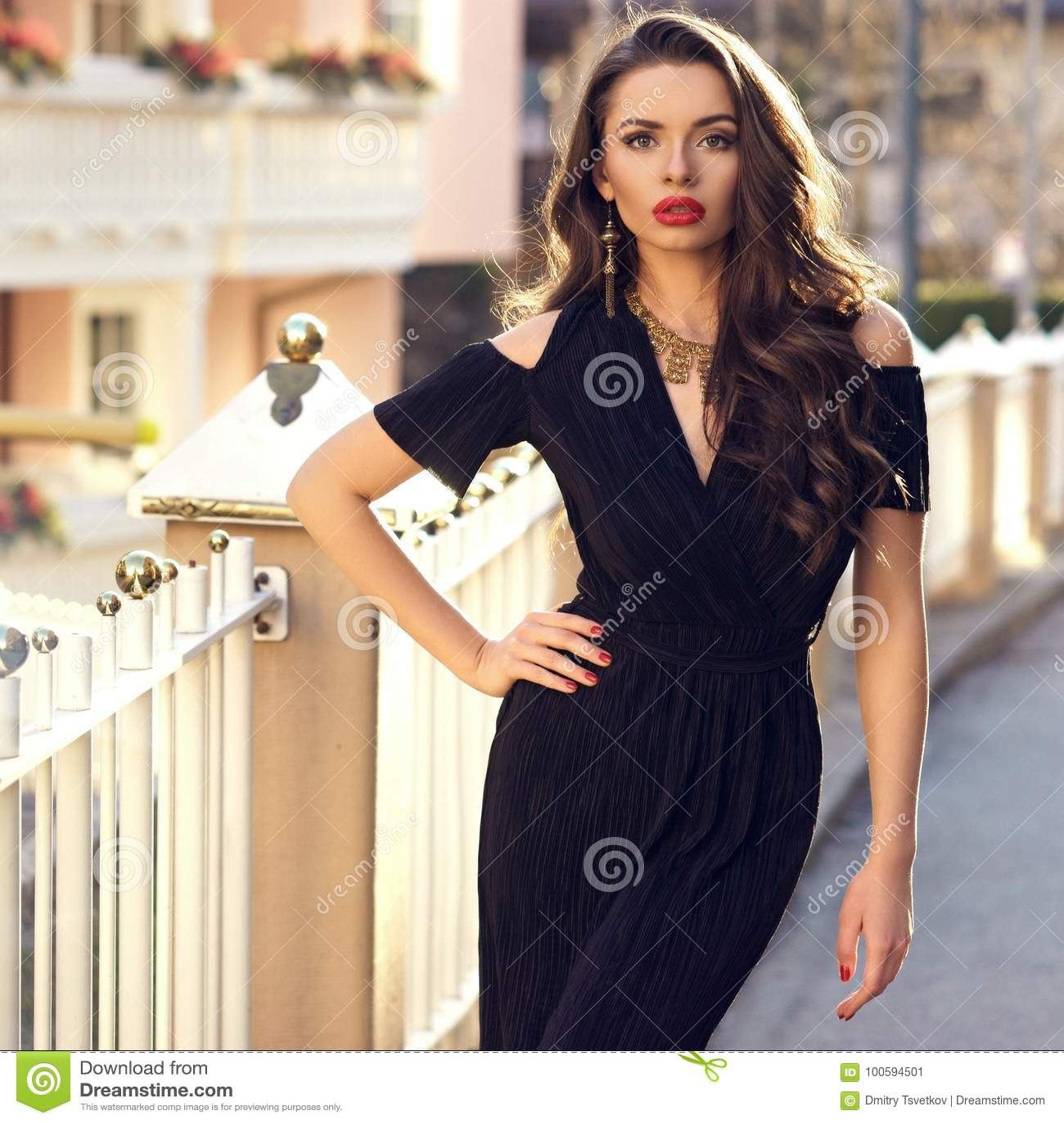 Herrliches weibliches Modell im schwarzen Kleid mit Ausschnitt schultert