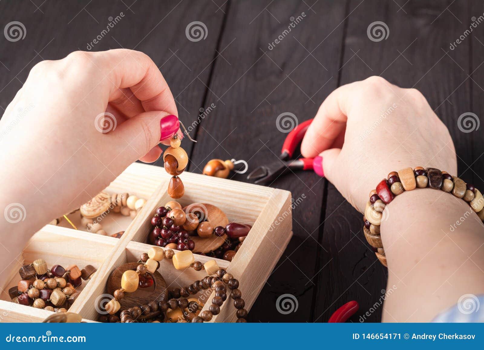 Herstellung des handgemachten Schmucks Kasten mit Perlen auf altem Holztisch