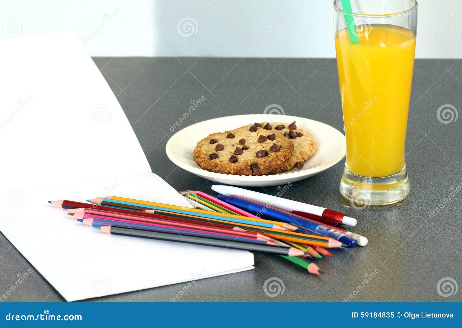 Herstellung von Hausarbeit: Schulbedarf mit leerem Notizbuch und Glas Orangensaft- und Schokoladensplitterplätzchen