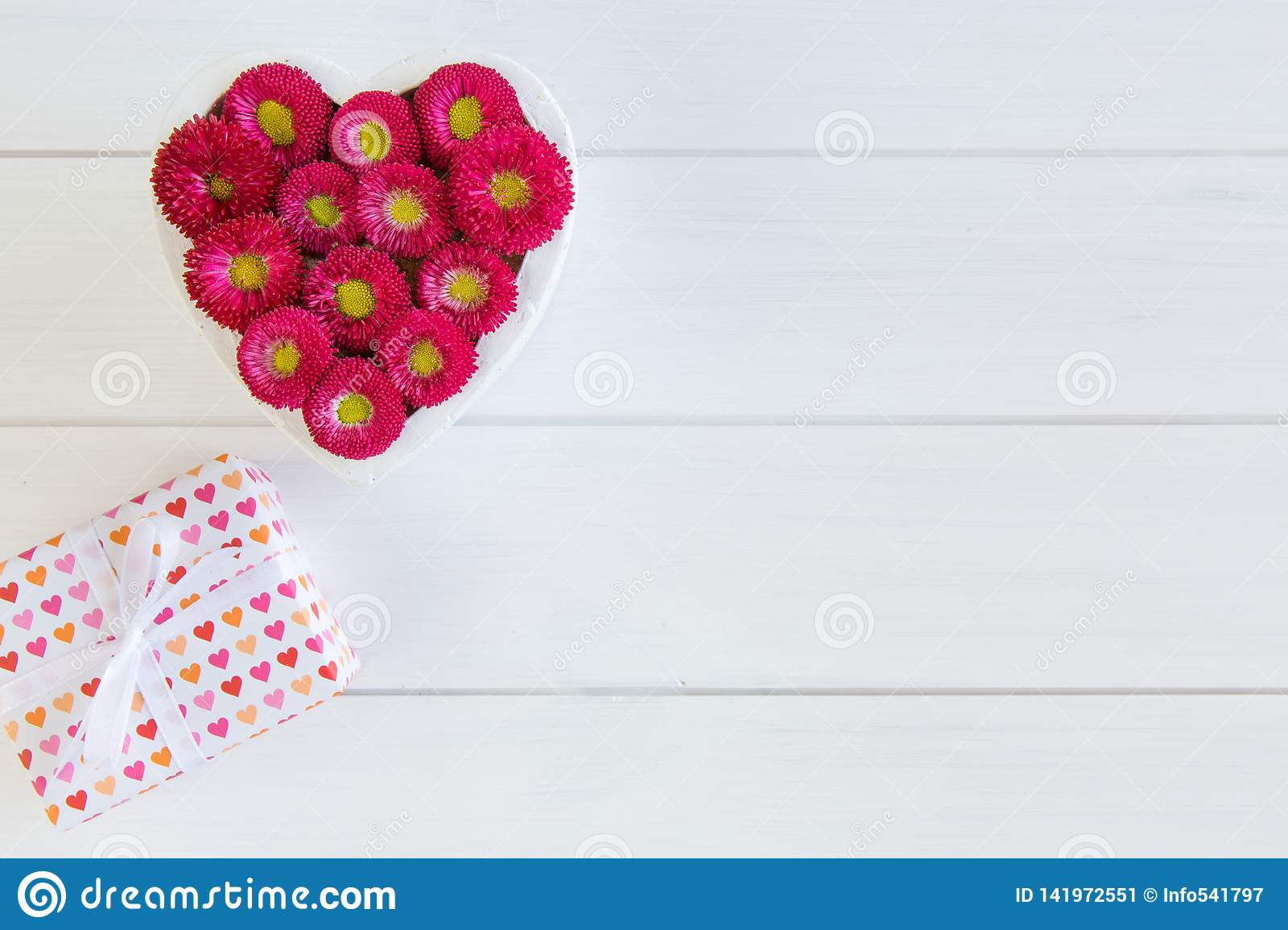 Heart from red Bellis and gift box with bow on wooden background in white