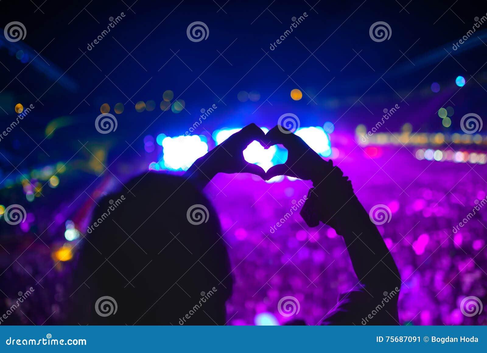 Herz formte Hände am Konzert, die Frau am Festival den Künstler und die Musik liebend