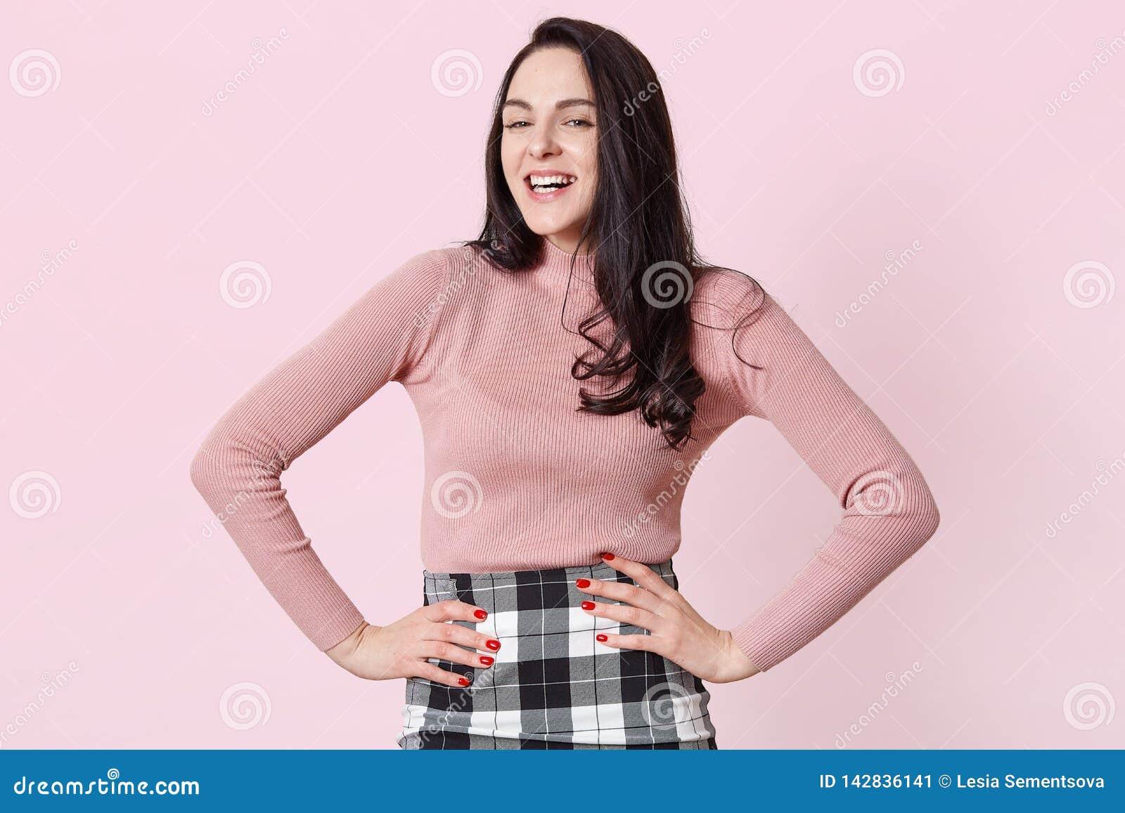 Het aanbiddelijke donkere haired meisje in roze overhemdsnad controleerde rok, die met handen stellen op heupen, lachend terwijl