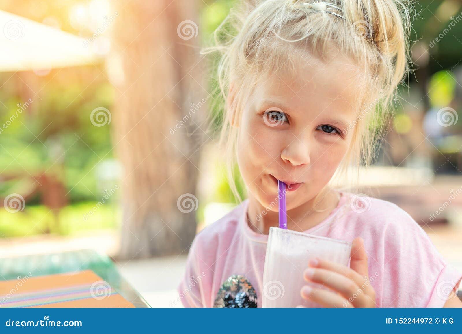 Het aanbiddelijke leuke portret die van het kleuter Kaukasische blonde meisje verse smakelijke aardbeimilkshake in openlucht nipp