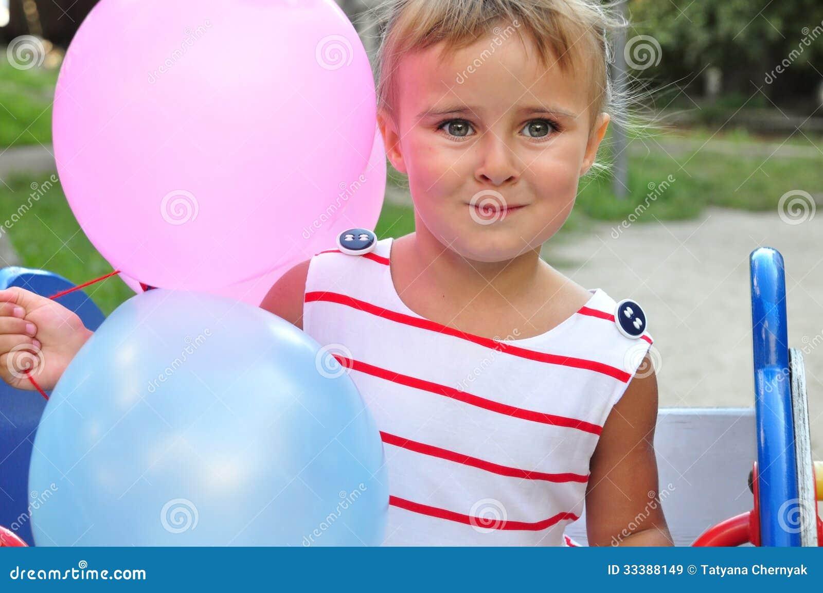Het aanbiddelijke meisje spelen met ballons