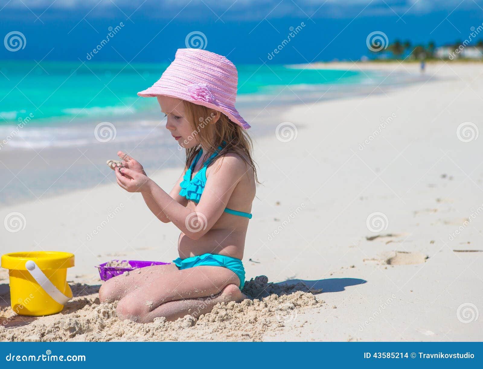 Het aanbiddelijke meisje spelen met zand op a