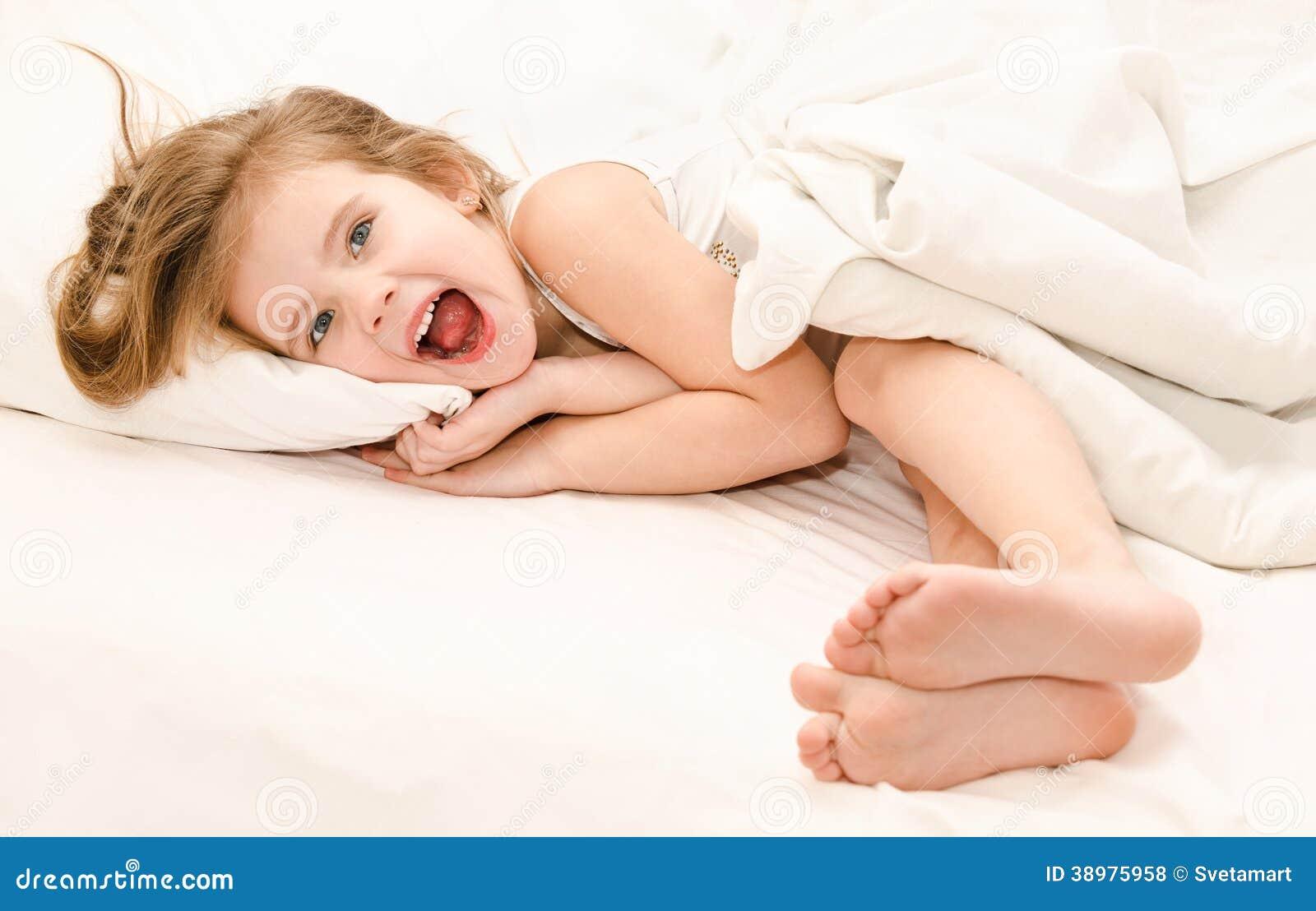 Het aanbiddelijke meisje waked omhoog in haar bed