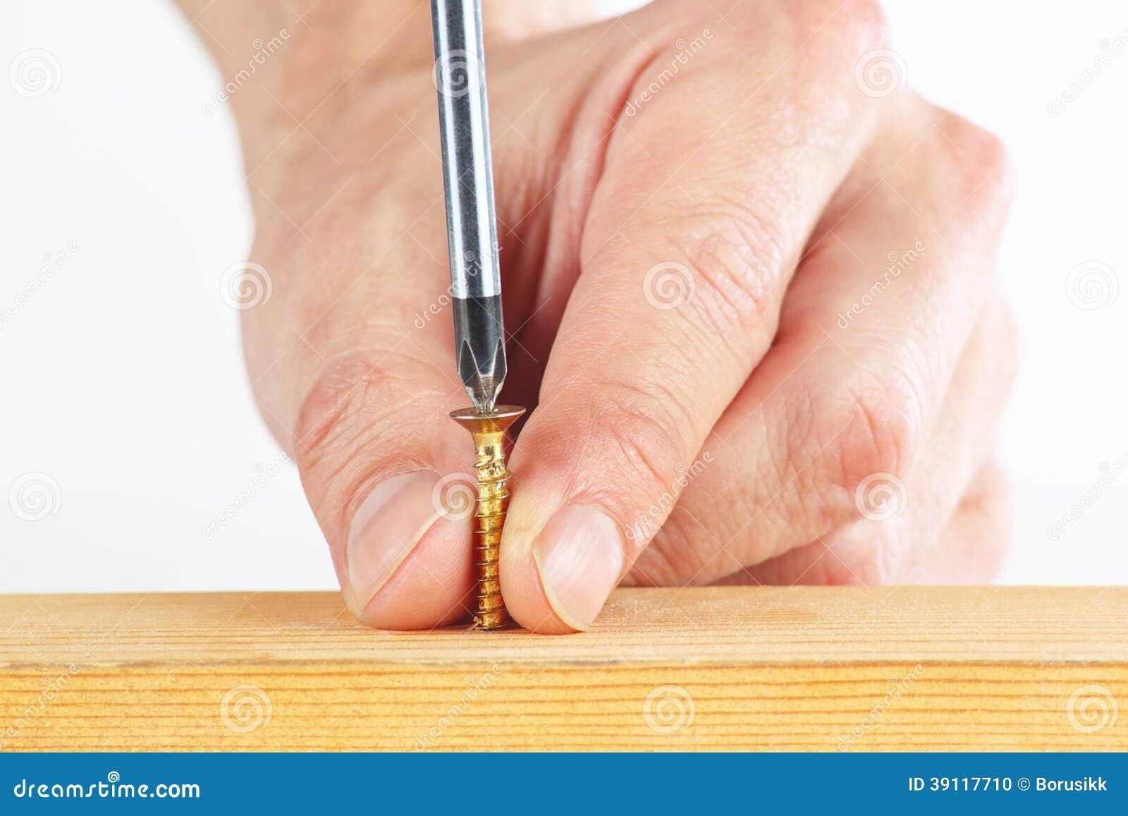 Het aanhalen van schroeven in een houten blok