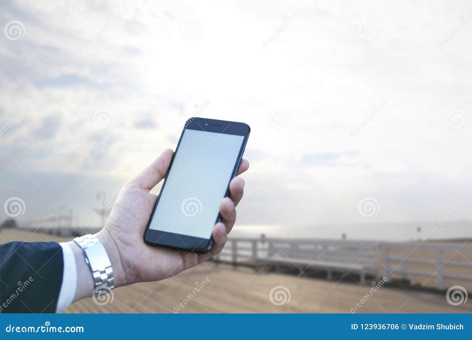 Het aanrakingsscherm van een mobiele telefoon, in de hand van een zakenman tegen de achtergrond van het overzees en de pijler Fot
