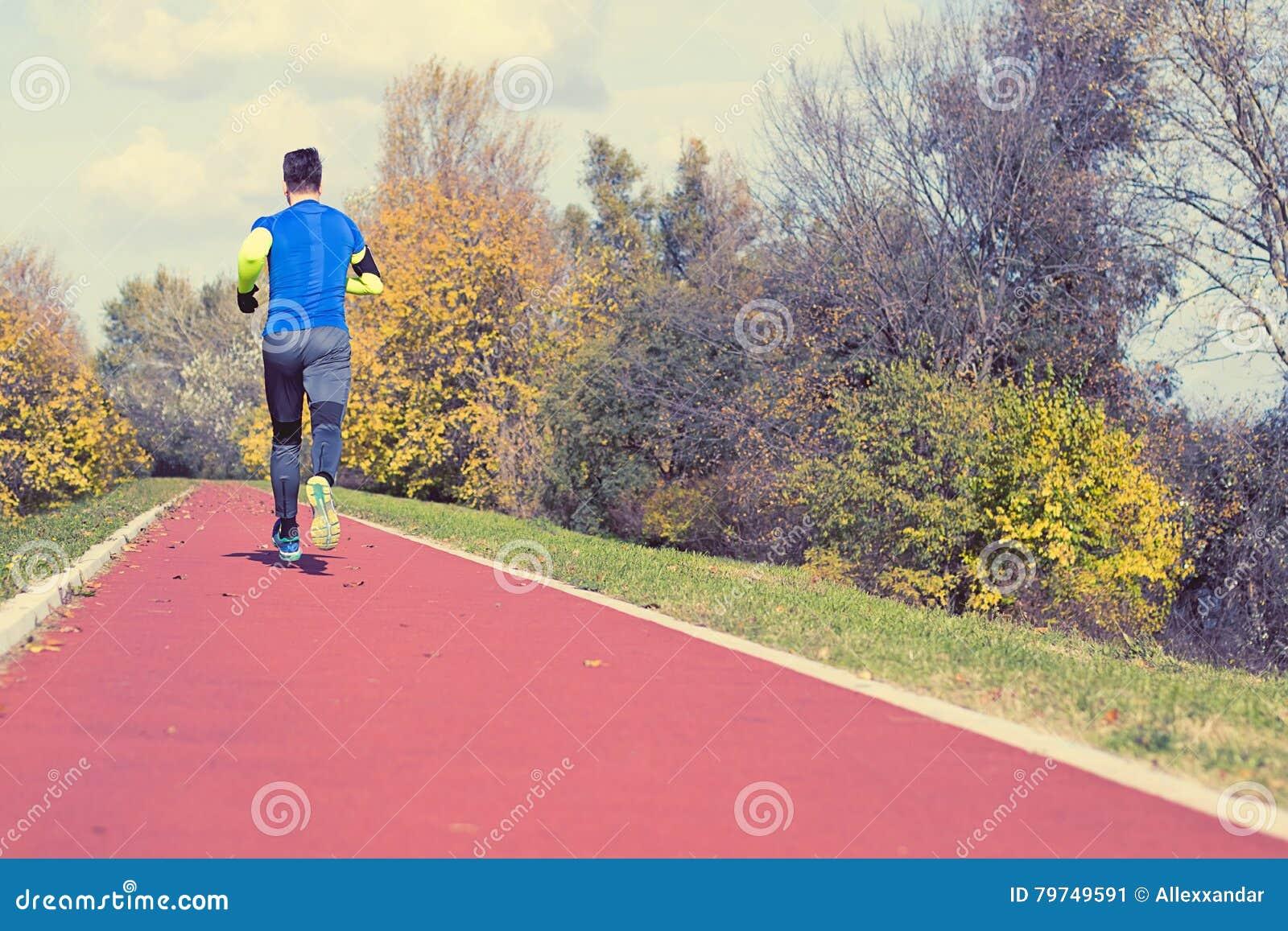 Het aanstoten in het park Autumn Edition Jonge mens in sporten kleding