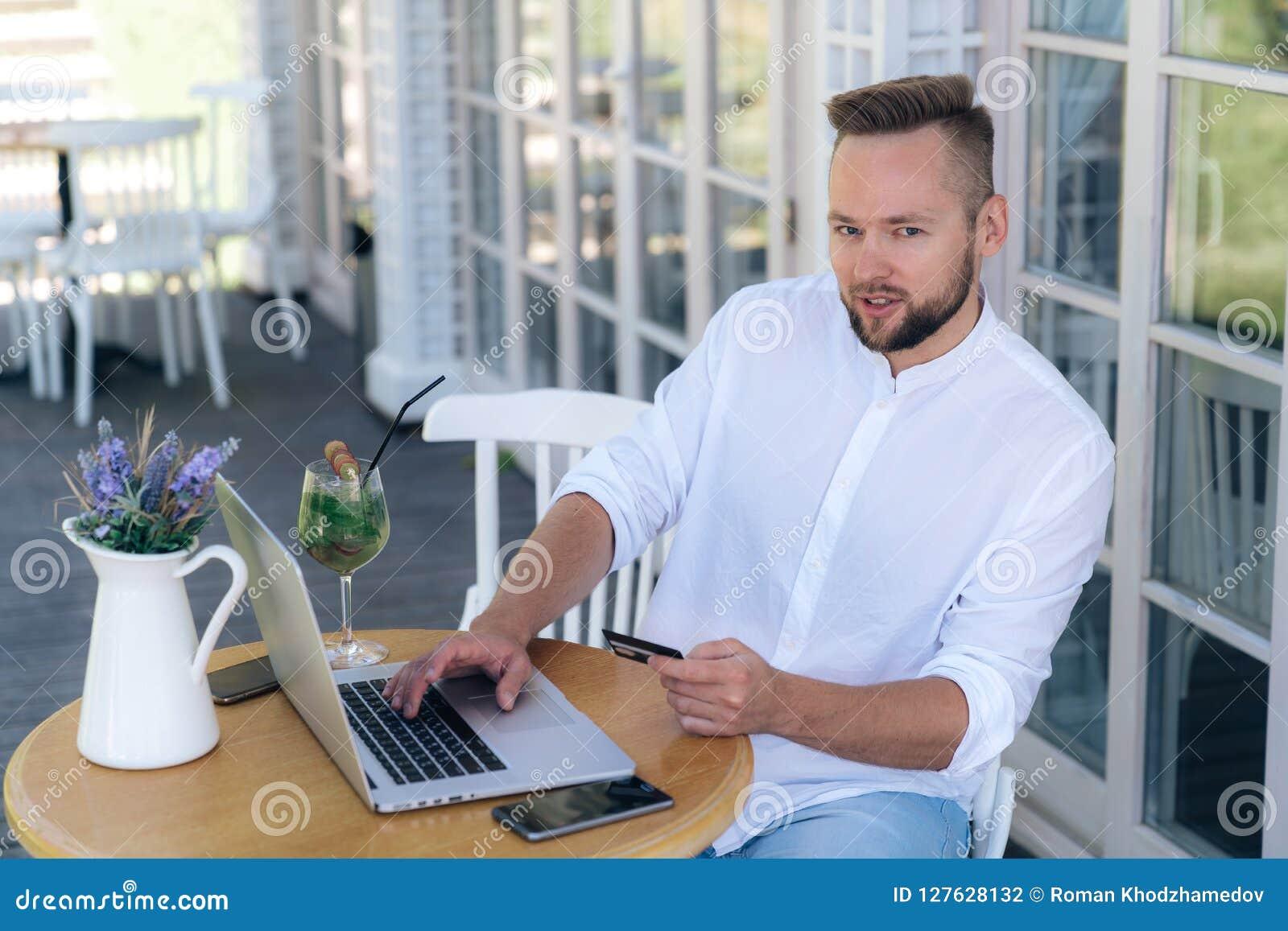 Het aantrekkelijk modieus jonge mensenwerk in een koffie, verricht betalingen van een betaalpas op Internet, gebruikt laptop en a