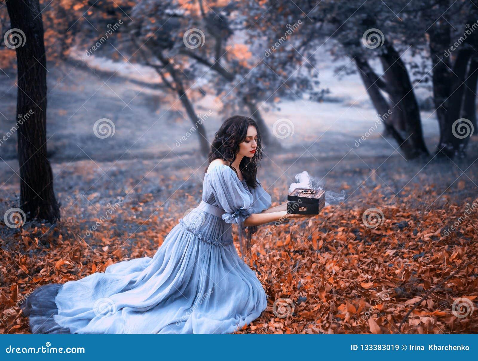 Het aantrekkelijke donkerbruine meisje zit in een donker bos op gevallen de herfst orazhevyh bladeren, gekleed in een grijze uits