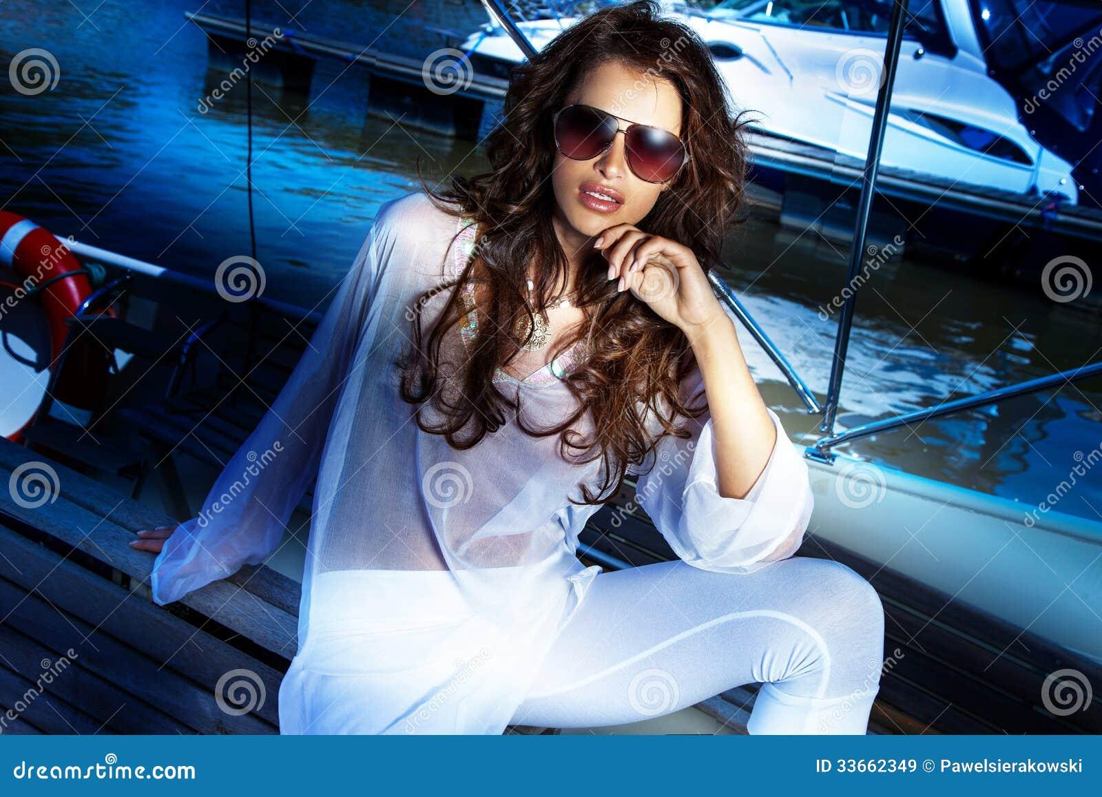 Het aantrekkelijke donkerbruine vrouw stellen in de zomerdag.