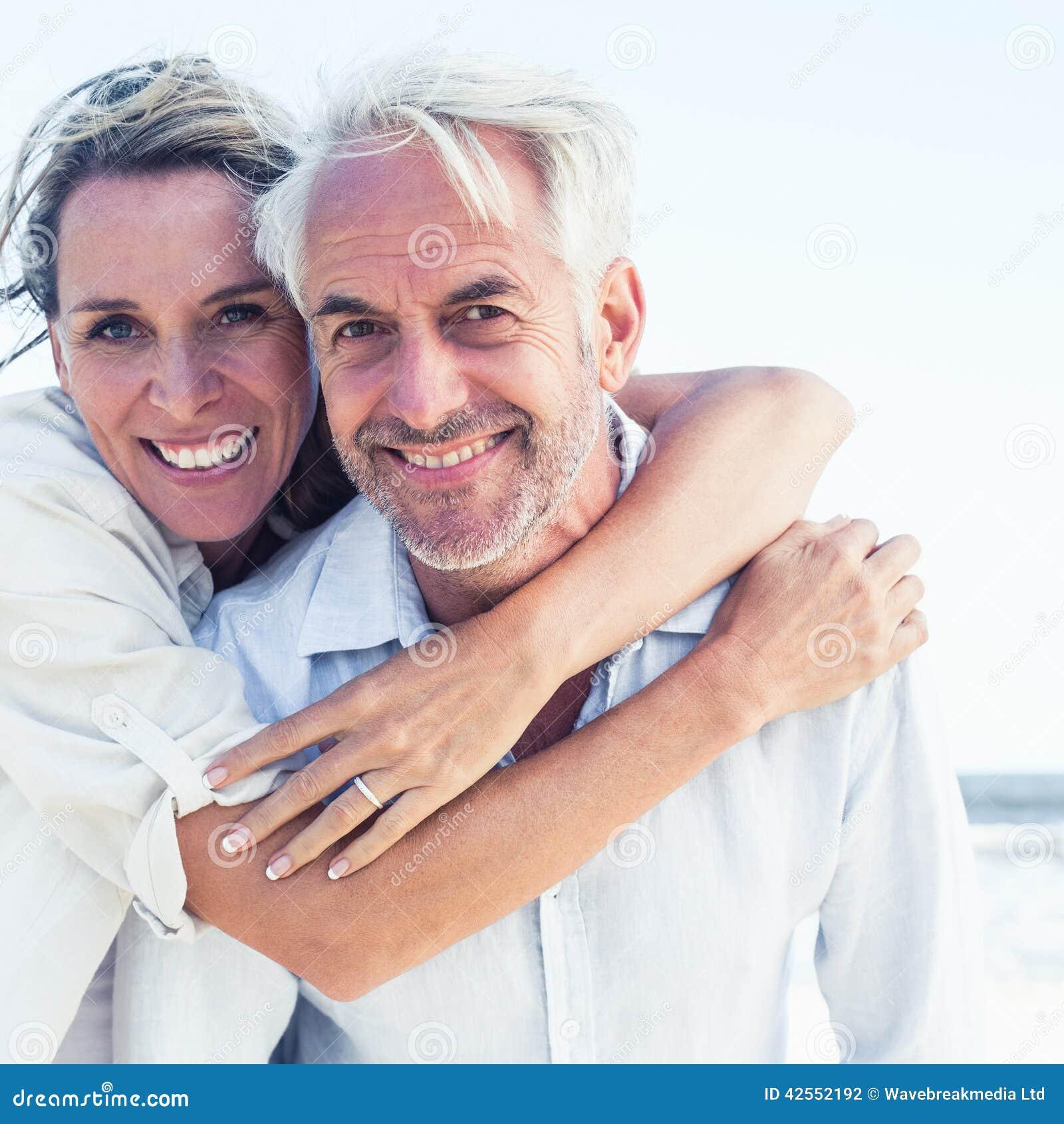 Het aantrekkelijke echtpaar stellen bij het strand