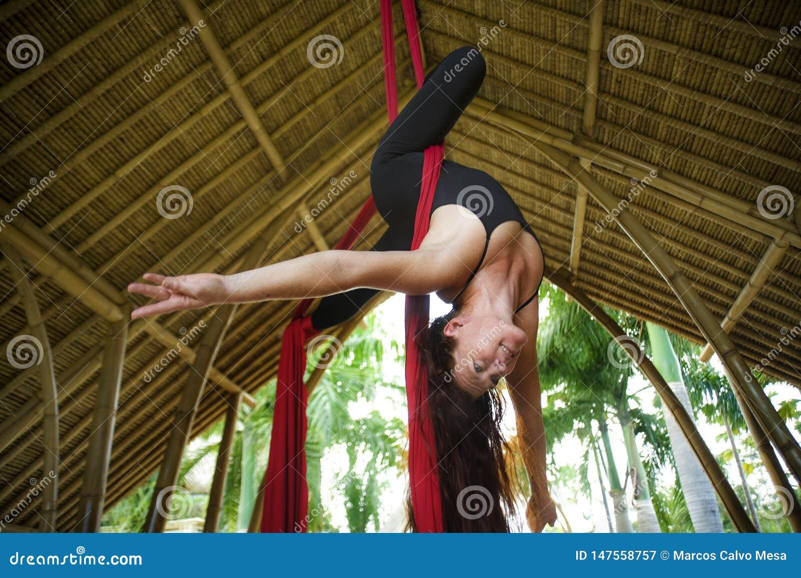 Het aantrekkelijke en atletische aerialistvrouw hangen van zijdestof die lucht het dansen training opleiding gelukkig bij mooie h