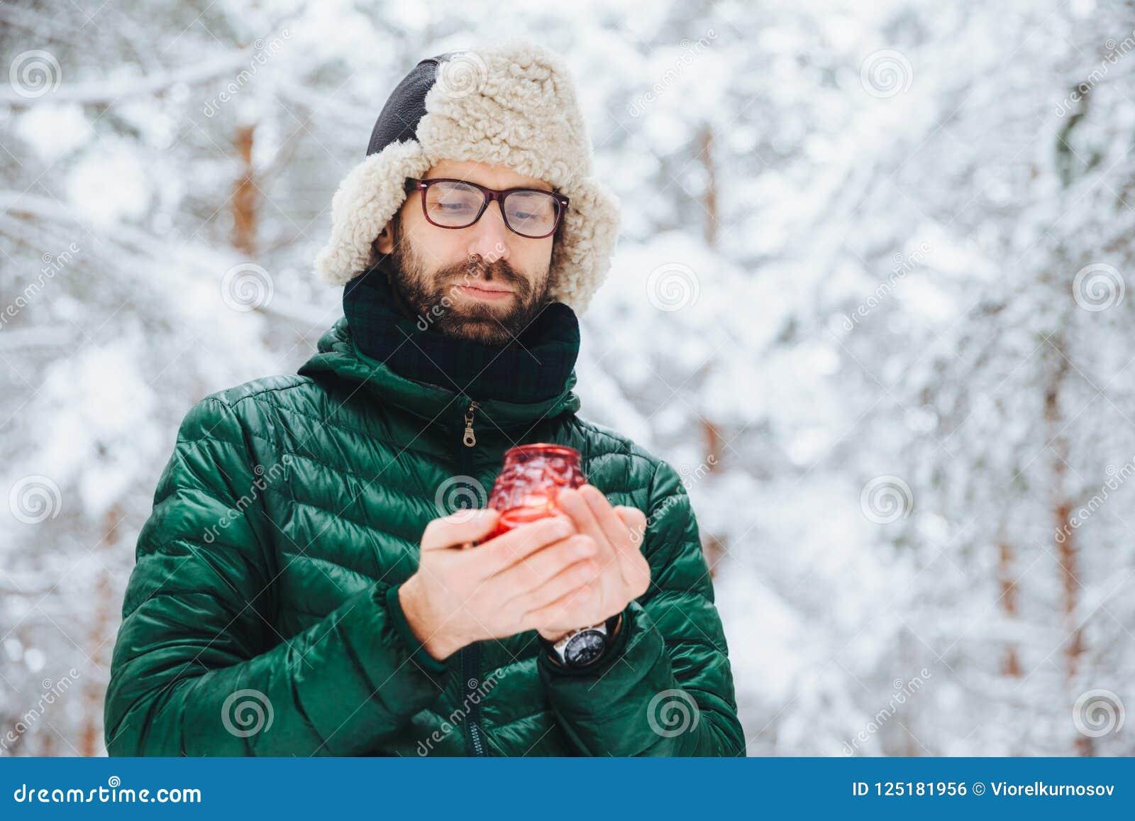 Het aantrekkelijke ernstige mannetje draagt warme de winterkleren, houdt kaars, bevindt zich tegen de winter de bosachtergrond, v