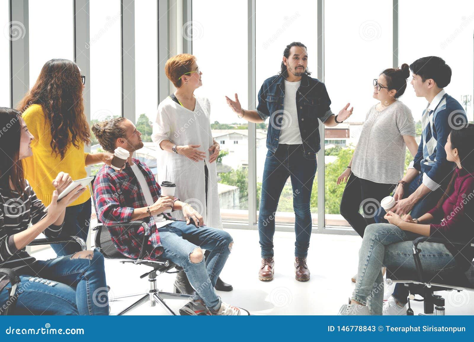 Het aantrekkelijke jonge multi-etnische groep spreken bij ontspant streek in koffiepauzetijd op kantoor Jonge Aziatische hipsterm