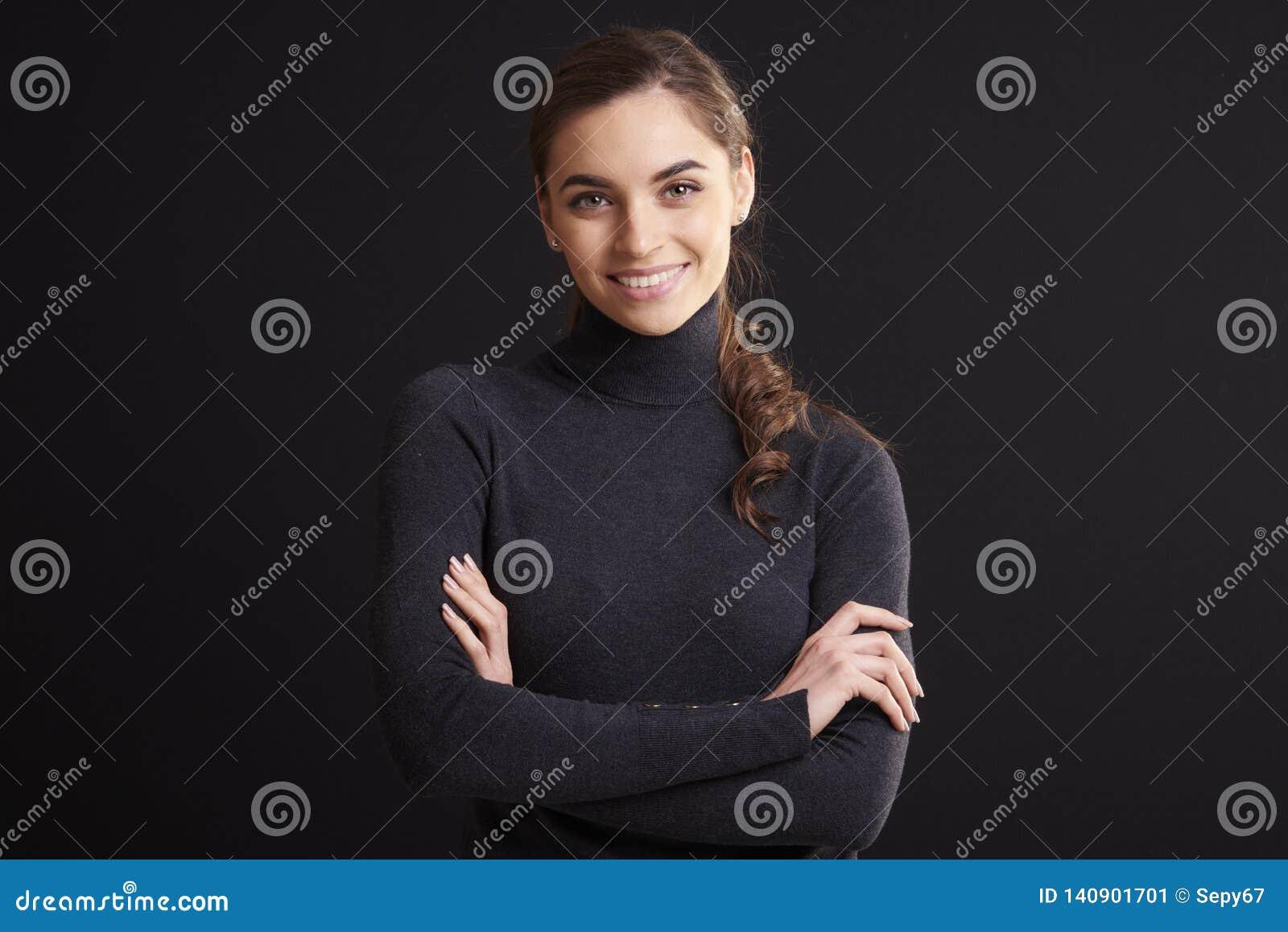 Het aantrekkelijke jonge portret van de vrouwenstudio terwijl status bij donkere achtergrond