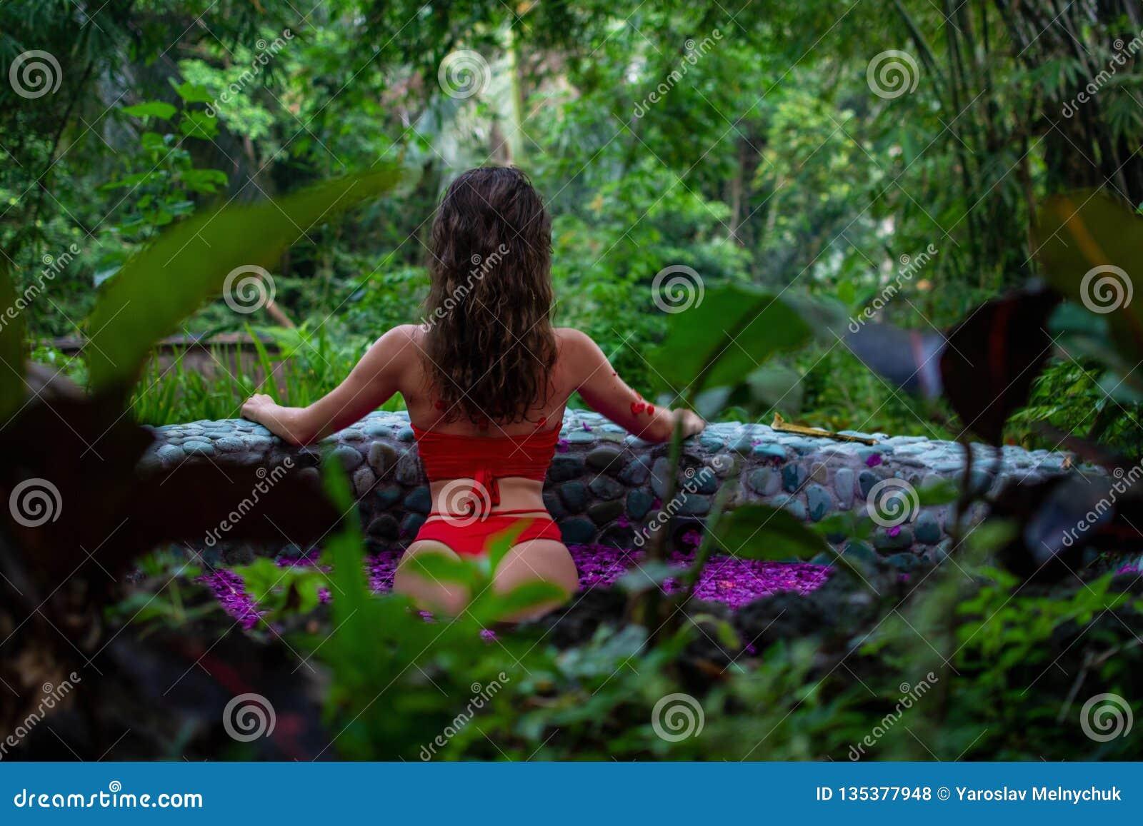 Het aantrekkelijke slanke meisje gaat in de wildernis achteruit Donkerbruin model binnen in de pool van bloemen Kuuroord, het ont
