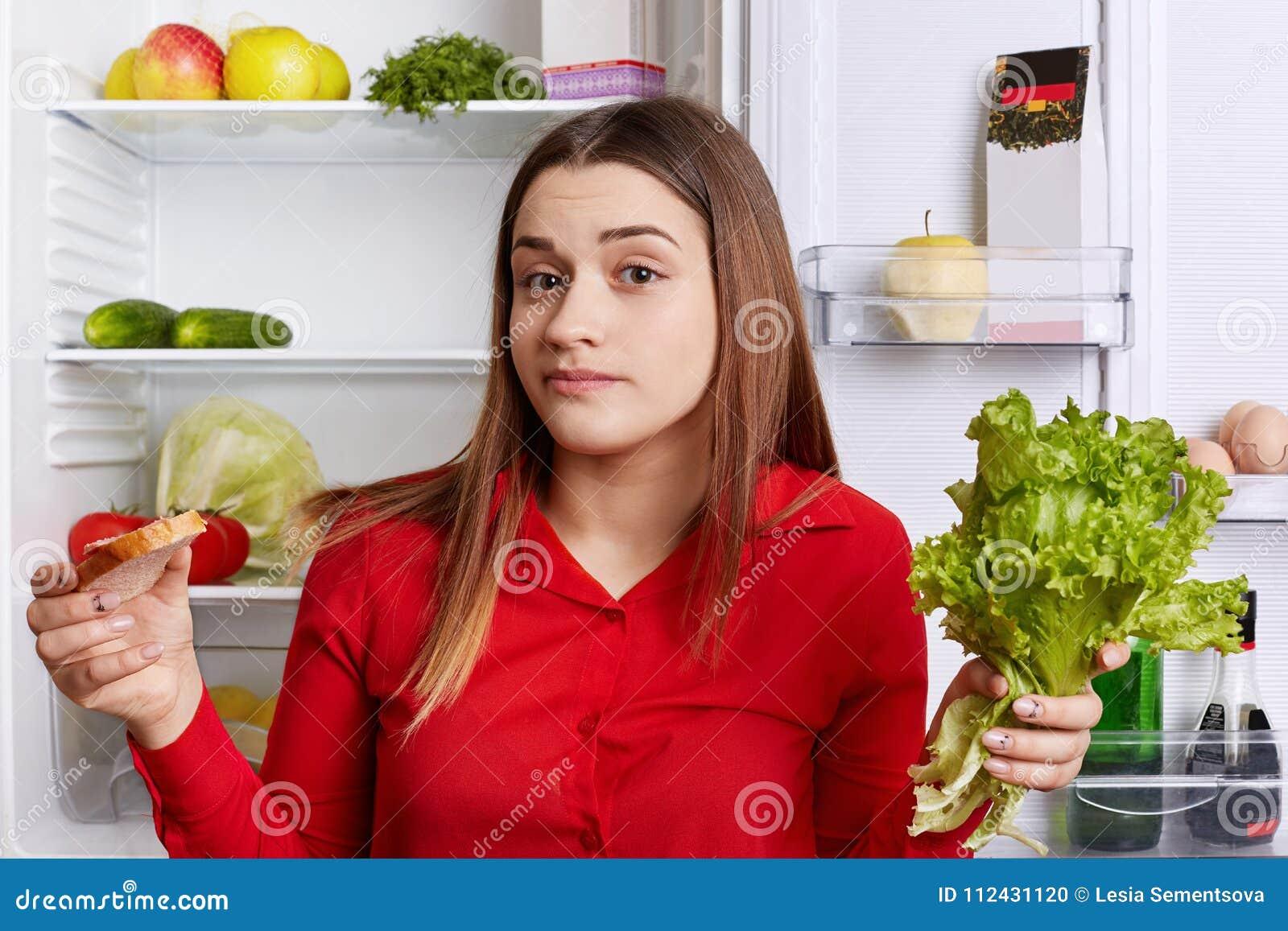 Het aarzelende jonge vrouwelijke model houdt sla en de sandwich in handen, doesn ` t weet wat om te kiezen, kan zich ` t aan diee