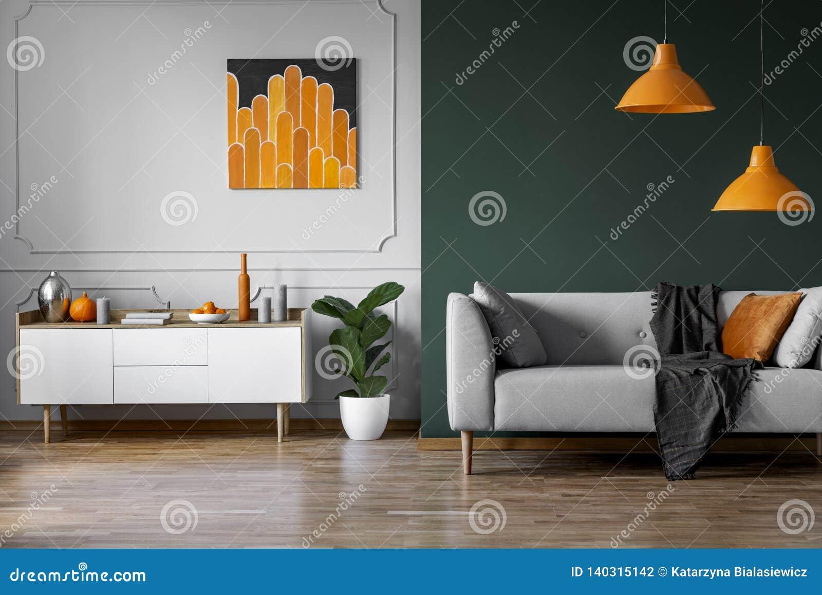 Het abstracte oranje schilderen op grijze muur van modieus woonkamerbinnenland met wit houten meubilair en grijze laag