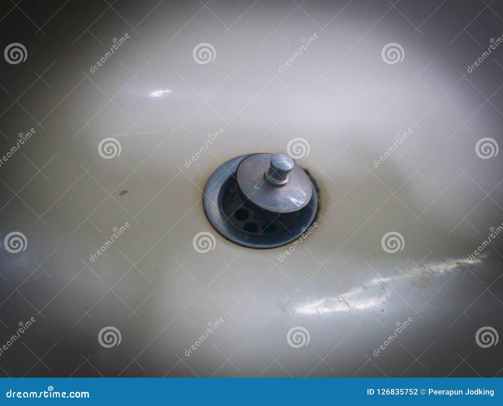 Het Abstracte Zilveren roestige gootsteengat in de witte ceramische rustige zonde,