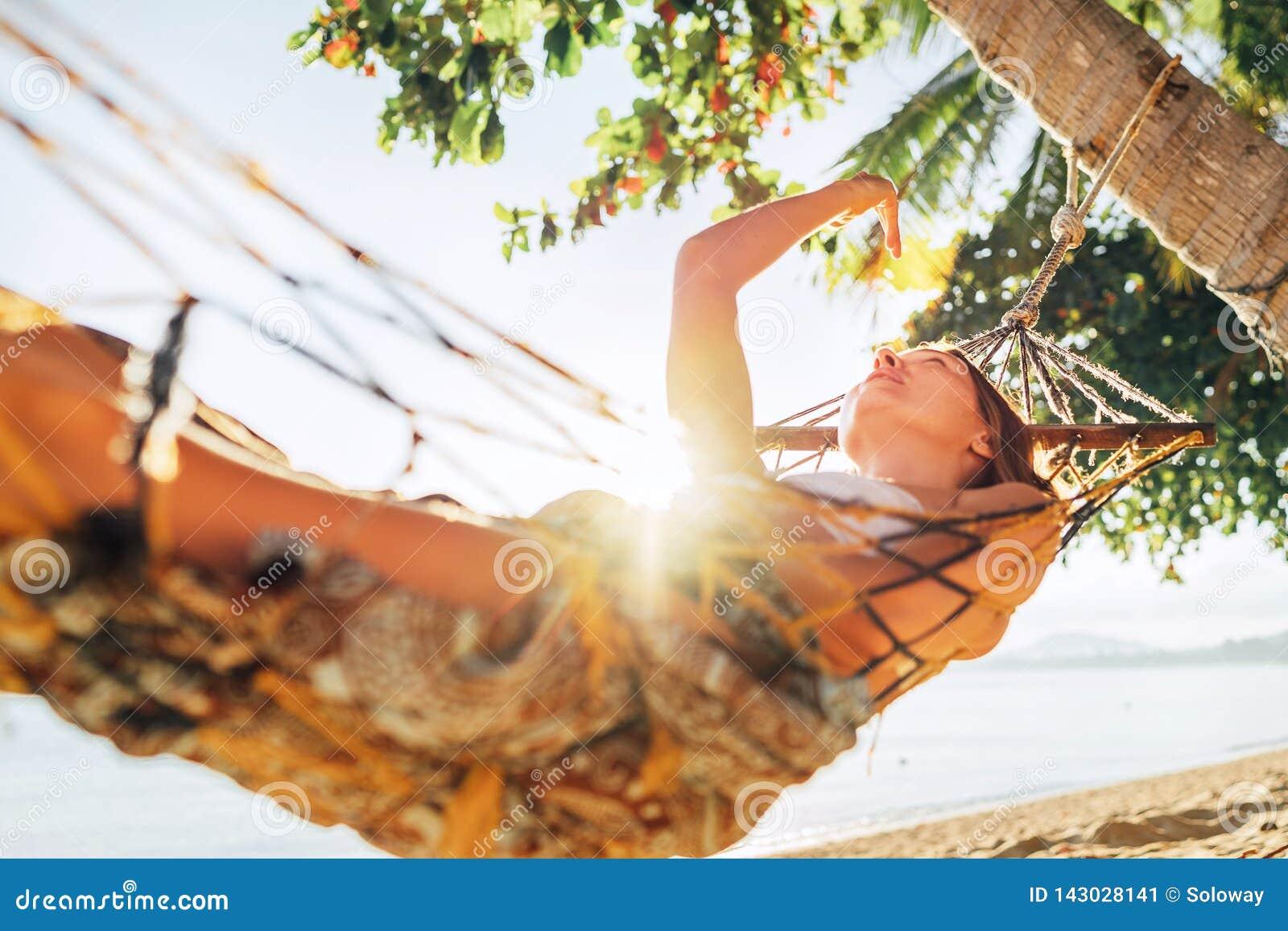 Het achteloze blonde longhaired vrouw ontspannen in hangmat scharnierend tussen palmen en het spelen met zonstralen