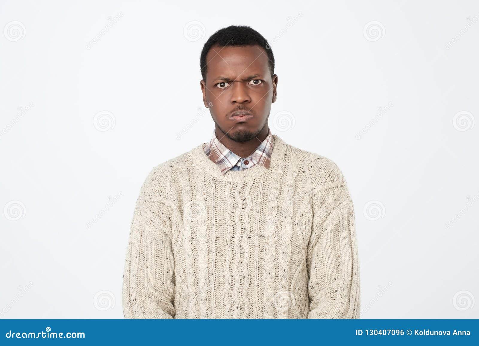 Het Afrikaanse Amerikaanse mannetje kleedde zich in warme sweater bekijkend camera met ernstige en droevige uitdrukking