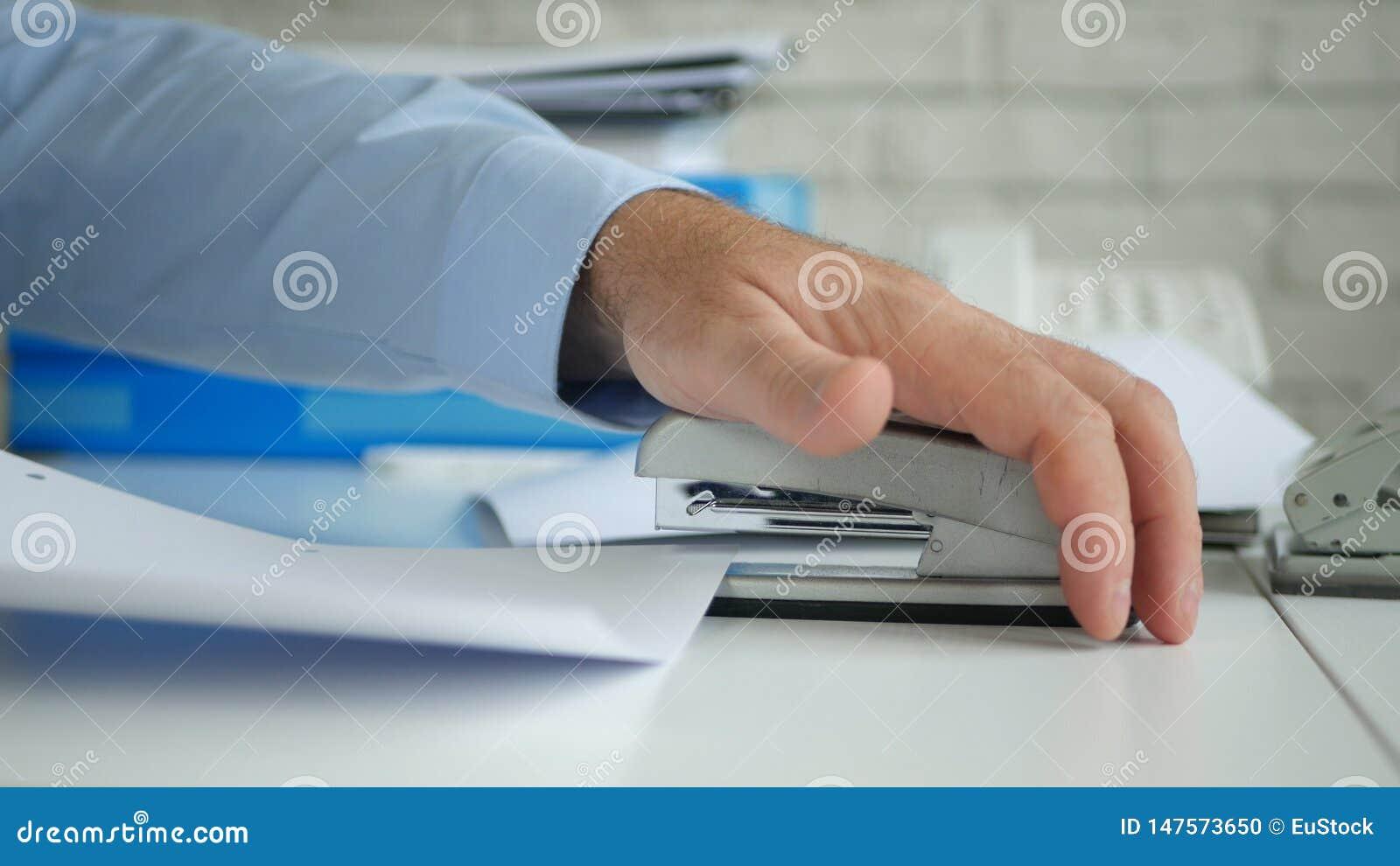Het Archiefcontracten en Documenten die van zakenmanjob in office een Nietmachine met behulp van