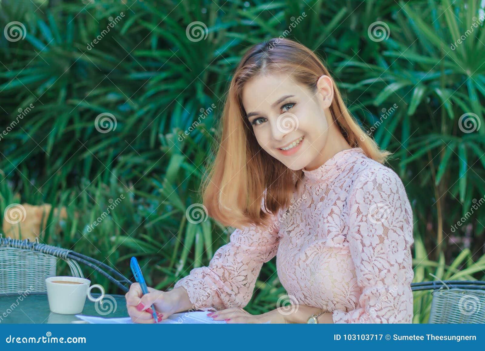 Het Aziatische bedrijfsvrouwen glimlachen werkend en schrijvend een boek en che