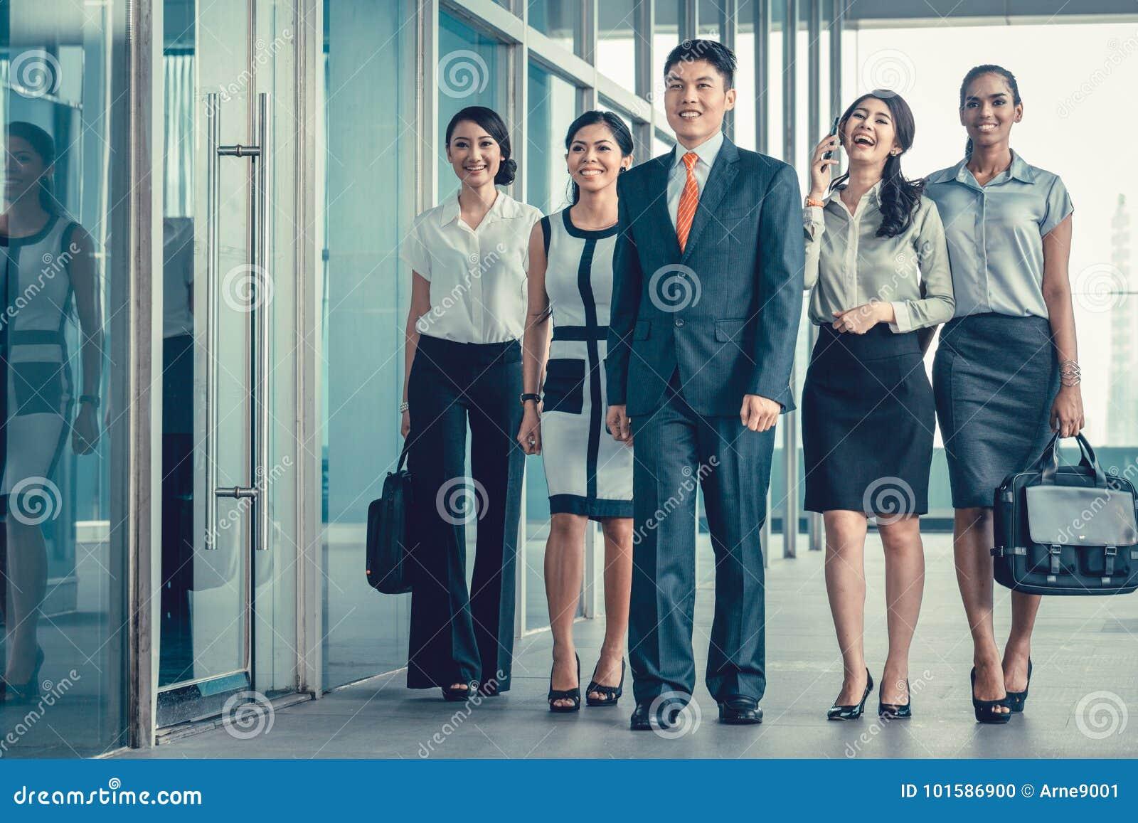 Het Aziatische commerciële team van stafmedewerkers die in bureau lopen schrikt zeer af
