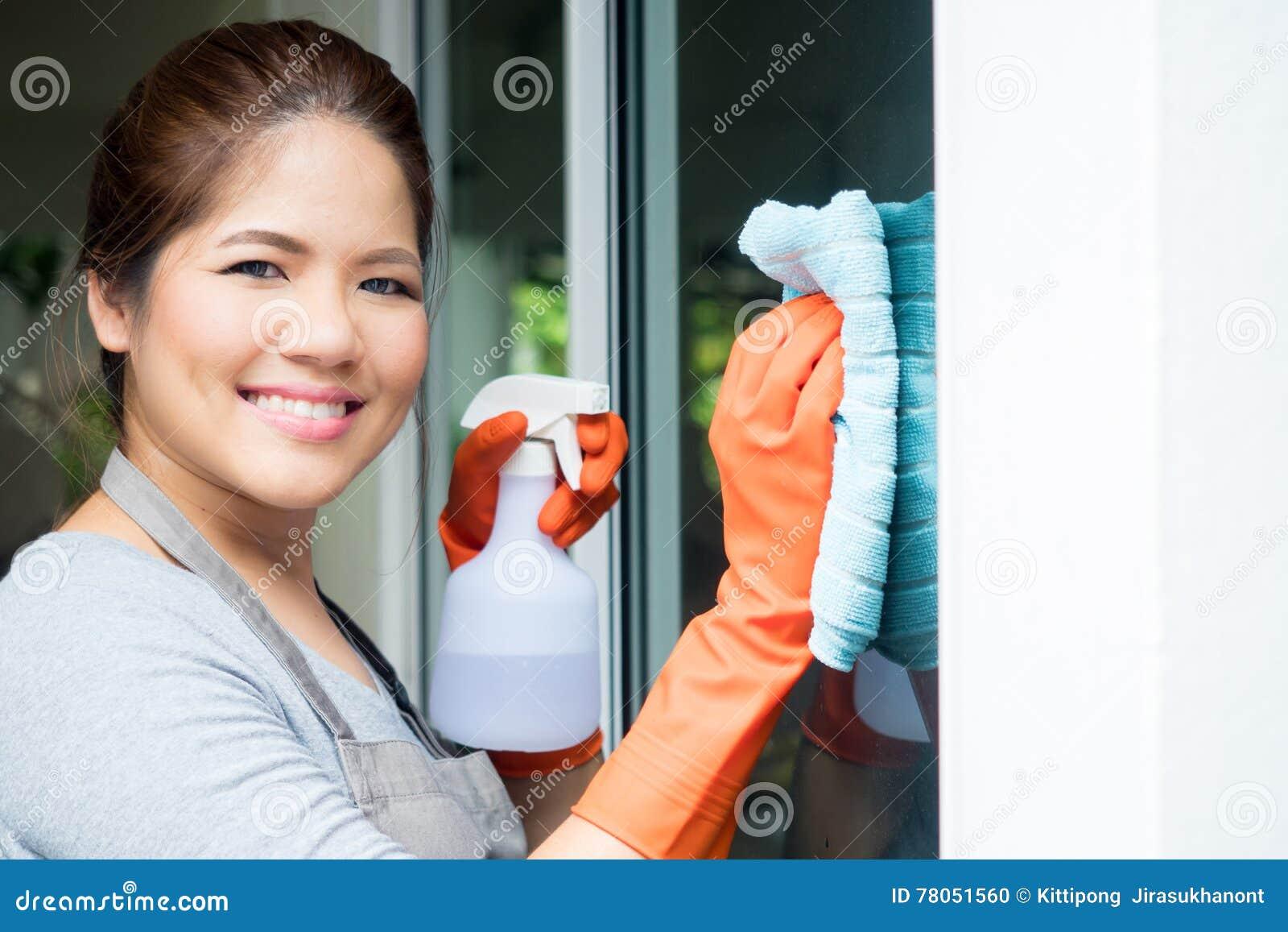 Het Aziatische huisvrouw schoonmaken op vensterglas