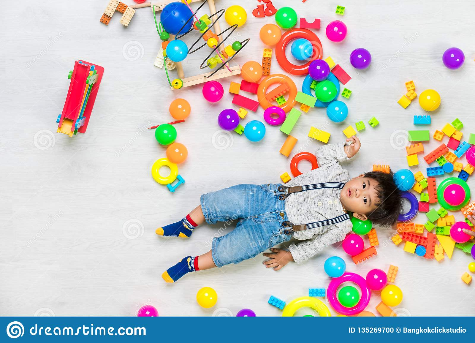 Het Aziatische jong geitje spelen met stuk speelgoed