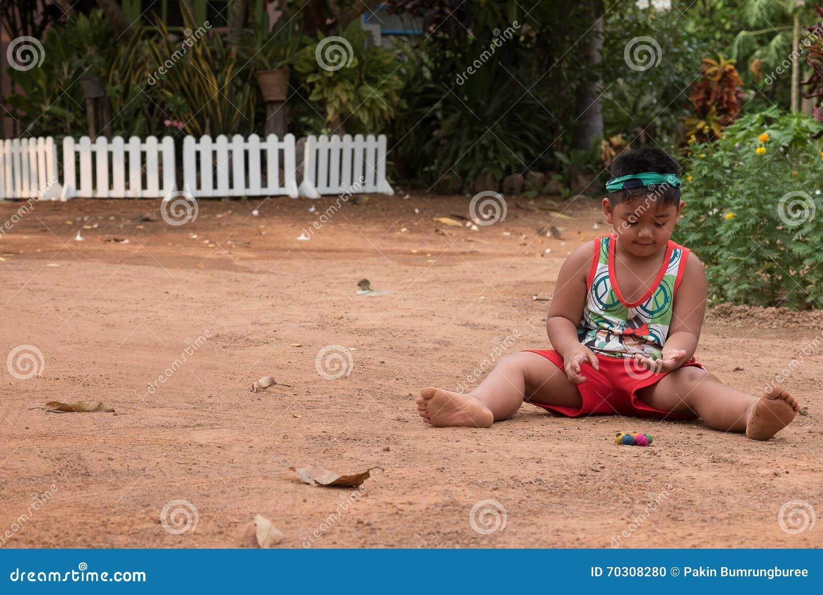 Het Aziatische kind spelen met zand en bal in de speelplaats
