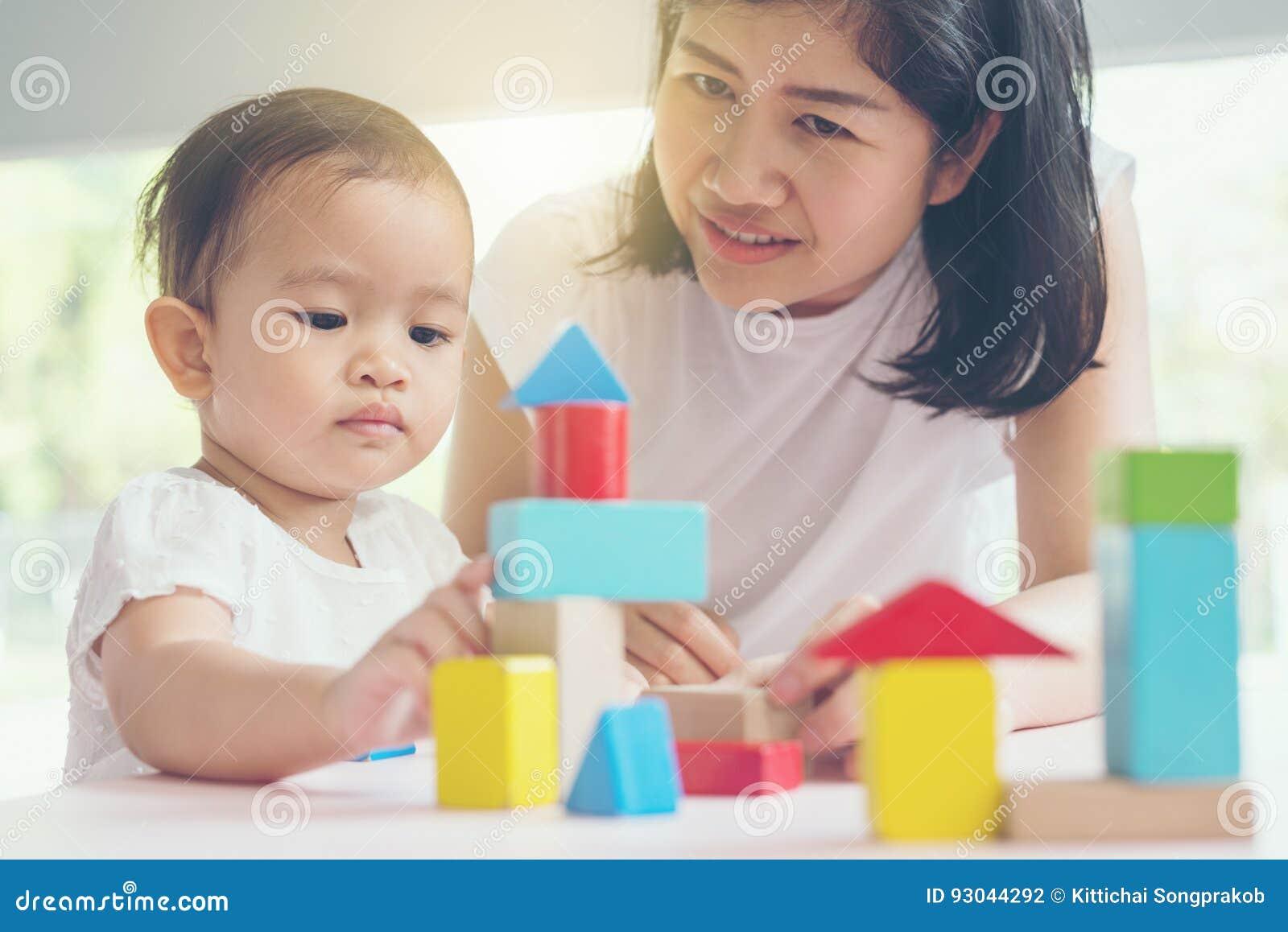 Het Aziatische mamma en meisjesjong geitje spelen met blokken Uitstekende gevolgen en