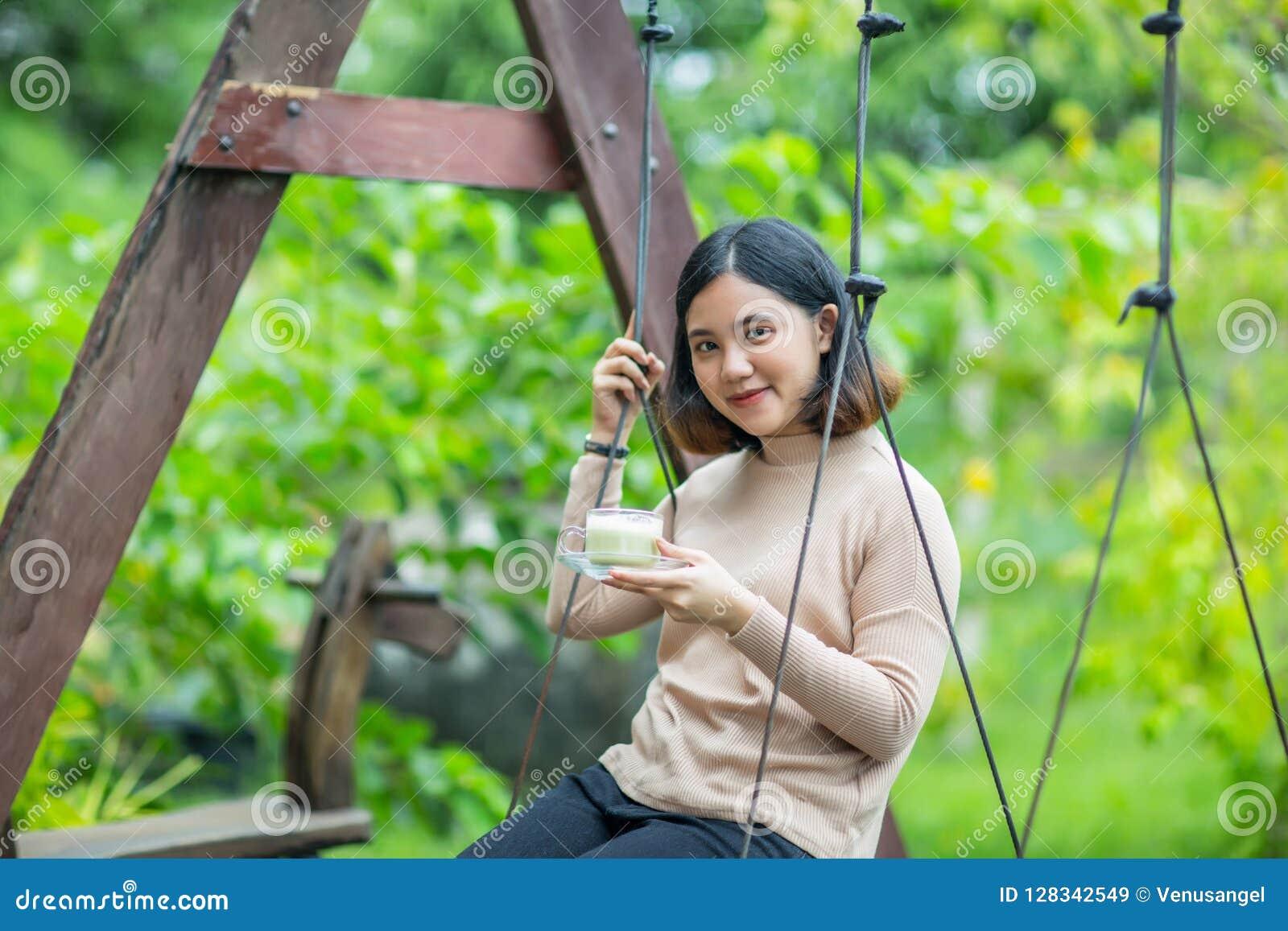 Het Aziatische meisje op houten schommeling en geniet van met haar groene thee