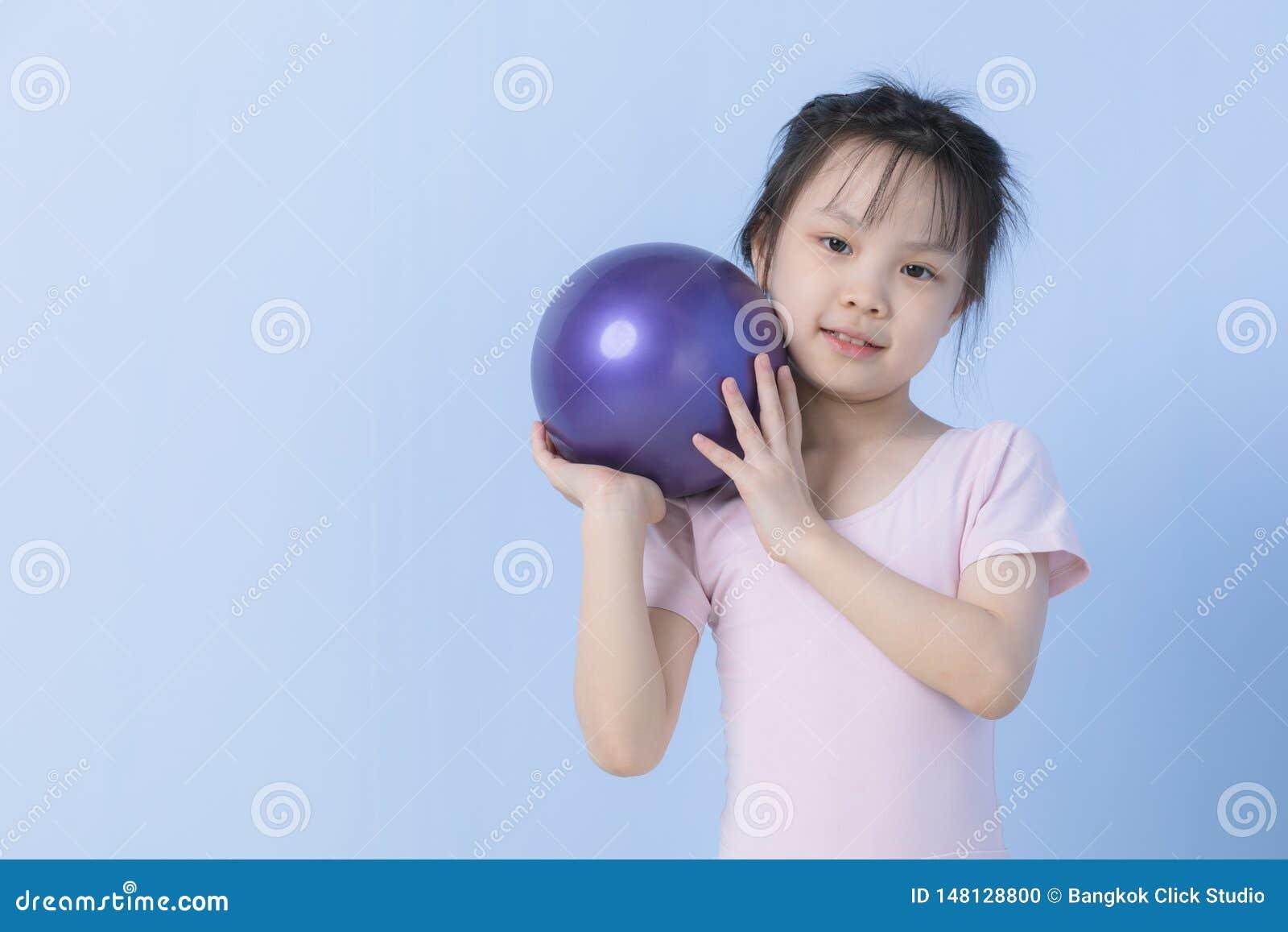 Het Aziatische meisje in roze kleding houdt bal