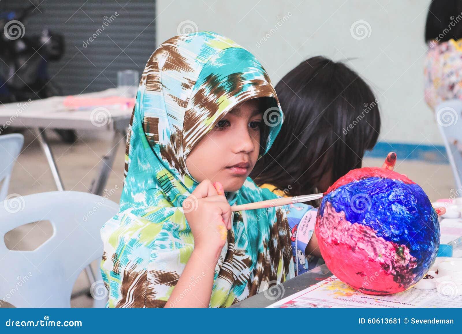 Het Aziatische Moslimjonge geitje schildert een kunstbal