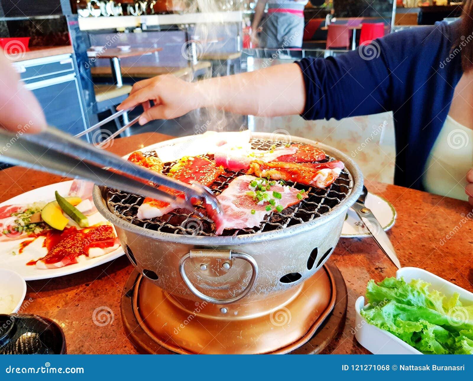 Het Aziatische ruwe gesneden rundvlees en het varkensvlees van de vrouwengrill op het hete roestvrij staalfornuis met rook