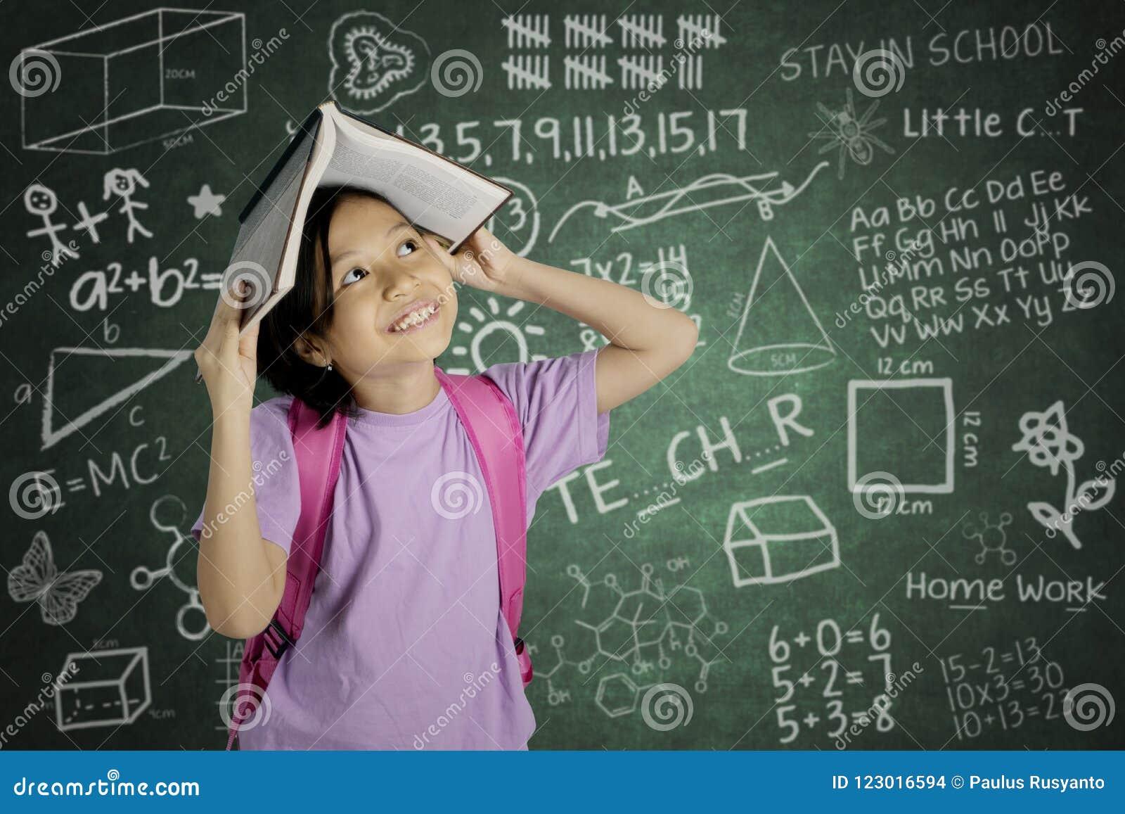 Het Aziatische schoolmeisje zet een open boek op haar hoofd