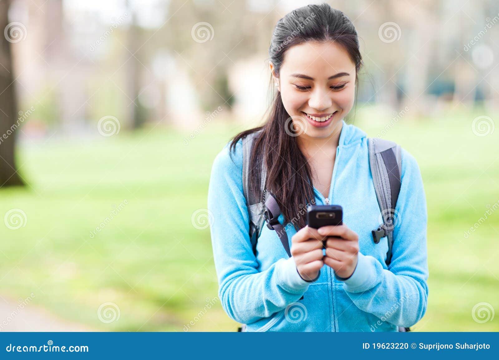 Het Aziatische student texting op de telefoon