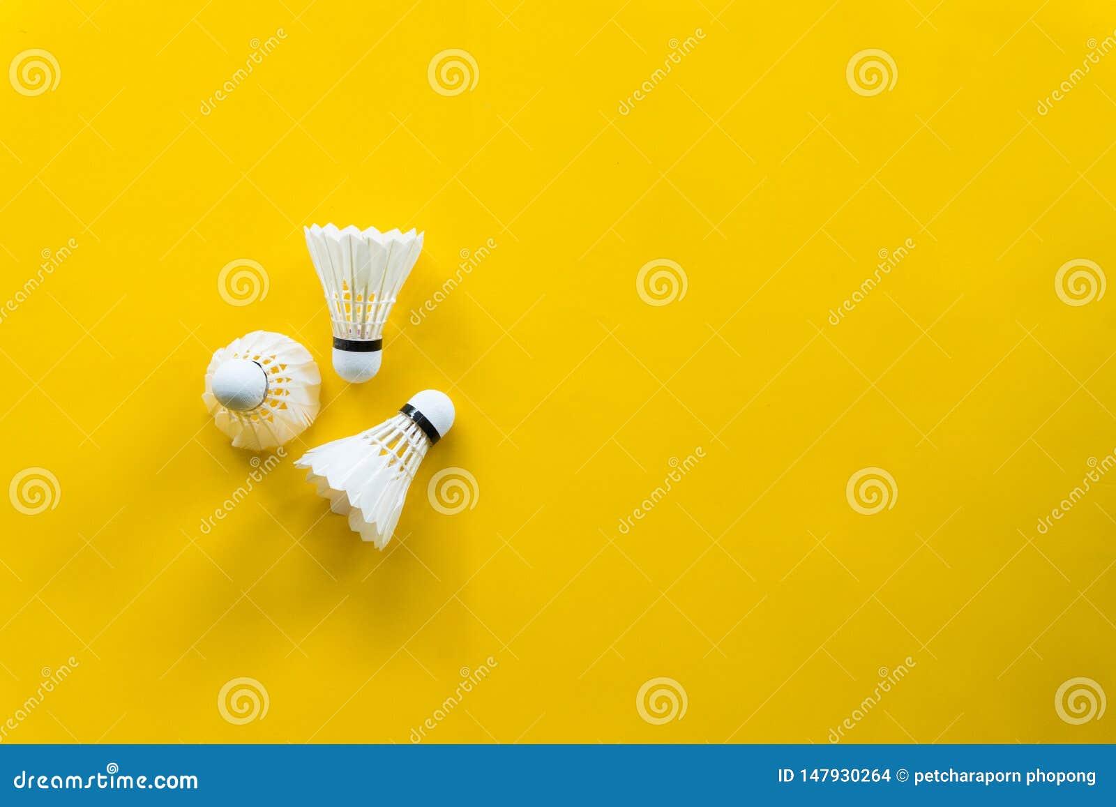 Het badminton van de pendelhaan met gele achtergrond