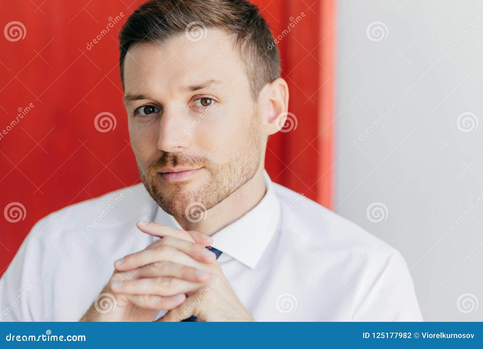 Het bebouwde beeld van zekere jonge mannelijke werknemer met varkenshaar, houdt handen samengeperst, gekleed in elegant wit overh