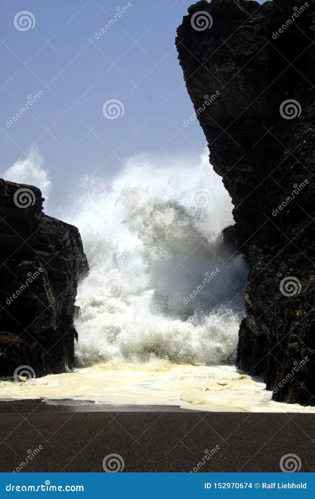 Het bedreigen van gevaarlijke witte zeedijk die door rotshiaat op het zwarte strand van het lavazand bij Vreedzame oceaan drukken