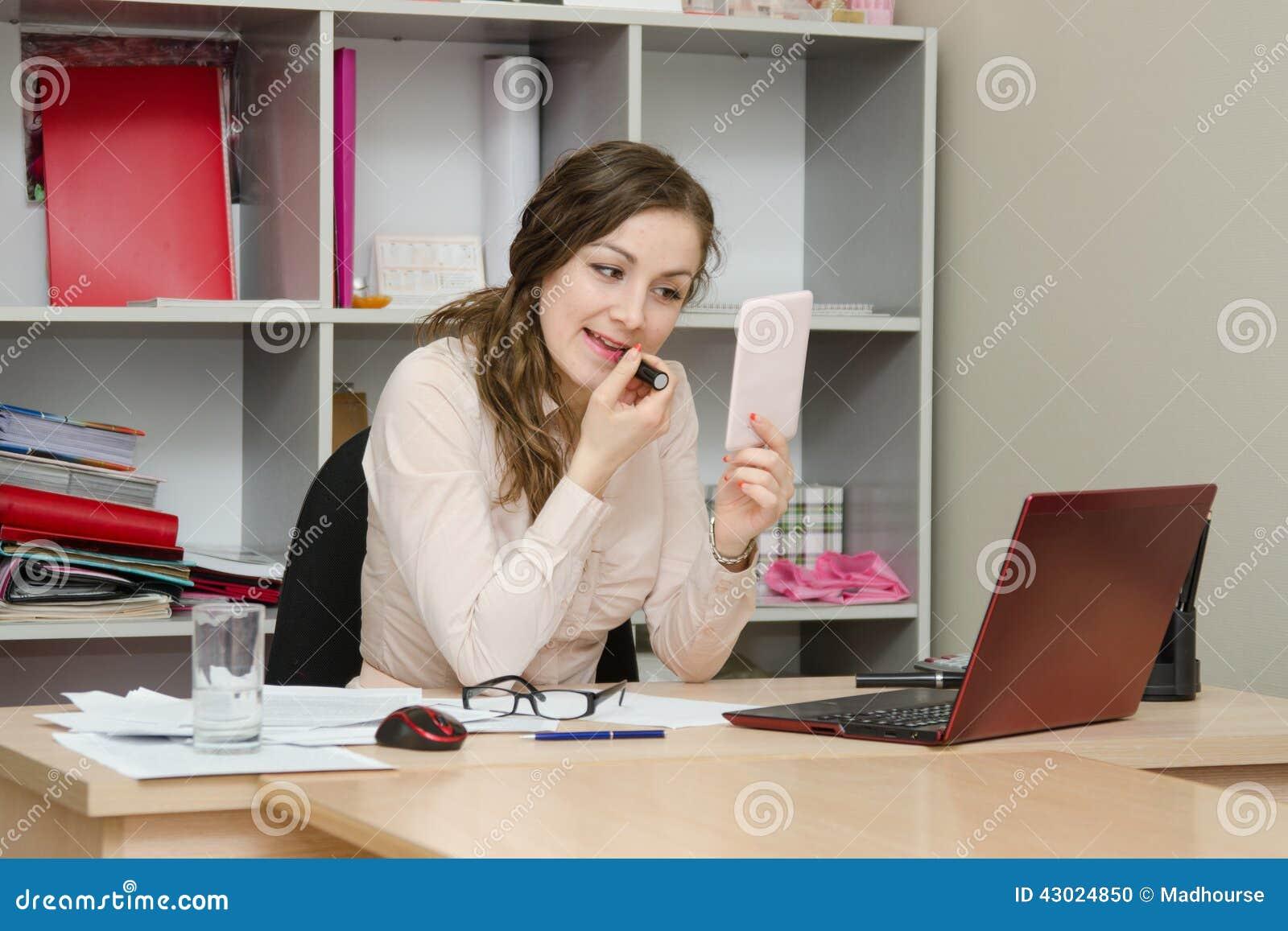 Het bedrijfsmeisje schildert lippen met lippenstift in het bureau