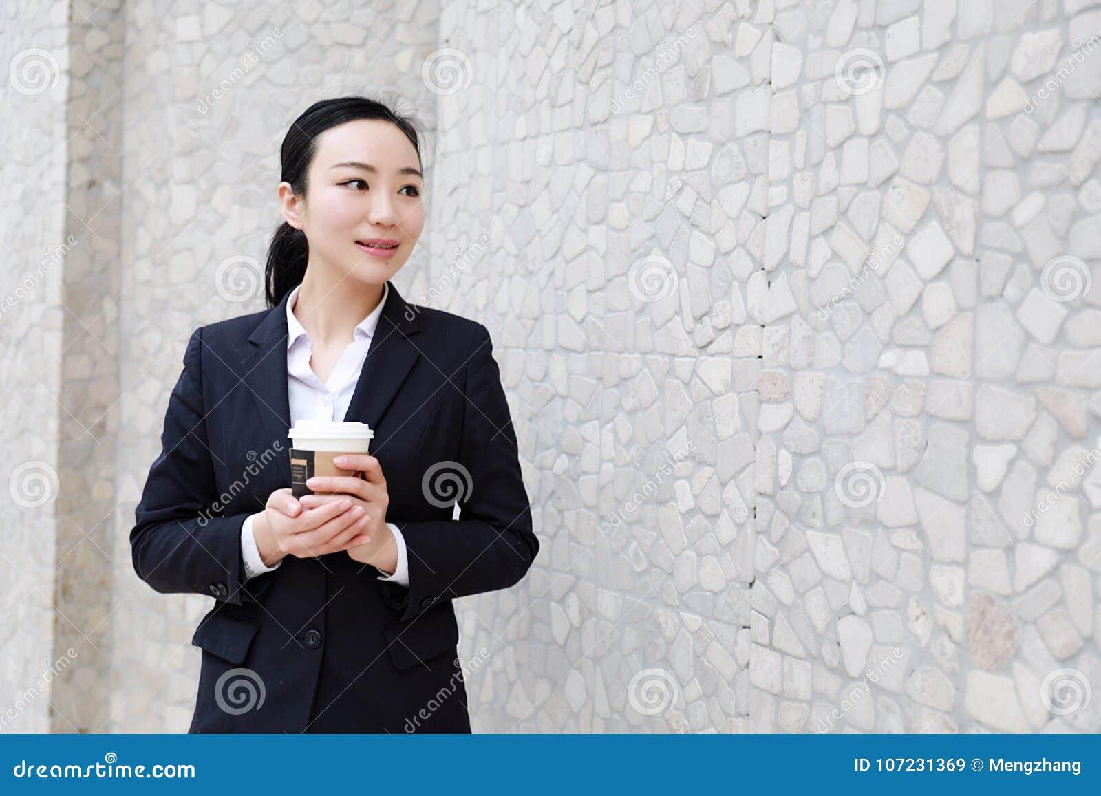 Het bedrijfsvrouw lopen het drinken koffie