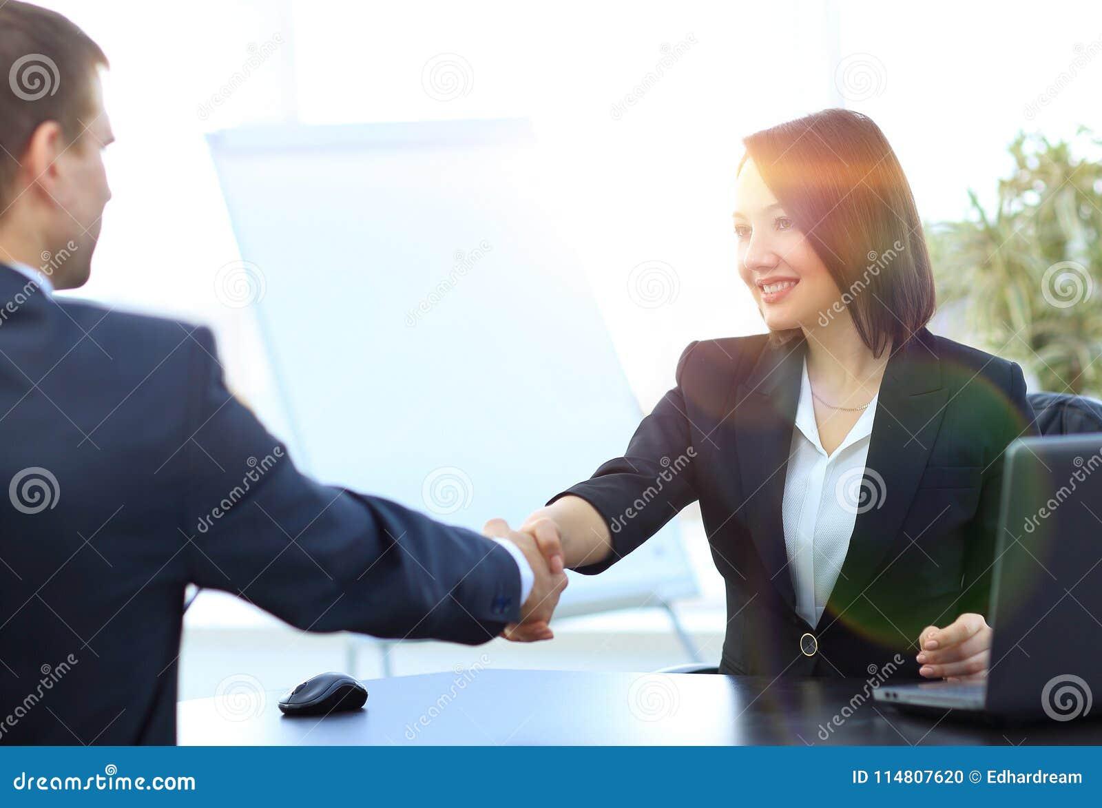 Het bedrijfsvrouw schudden handen met een partner over een Bureau