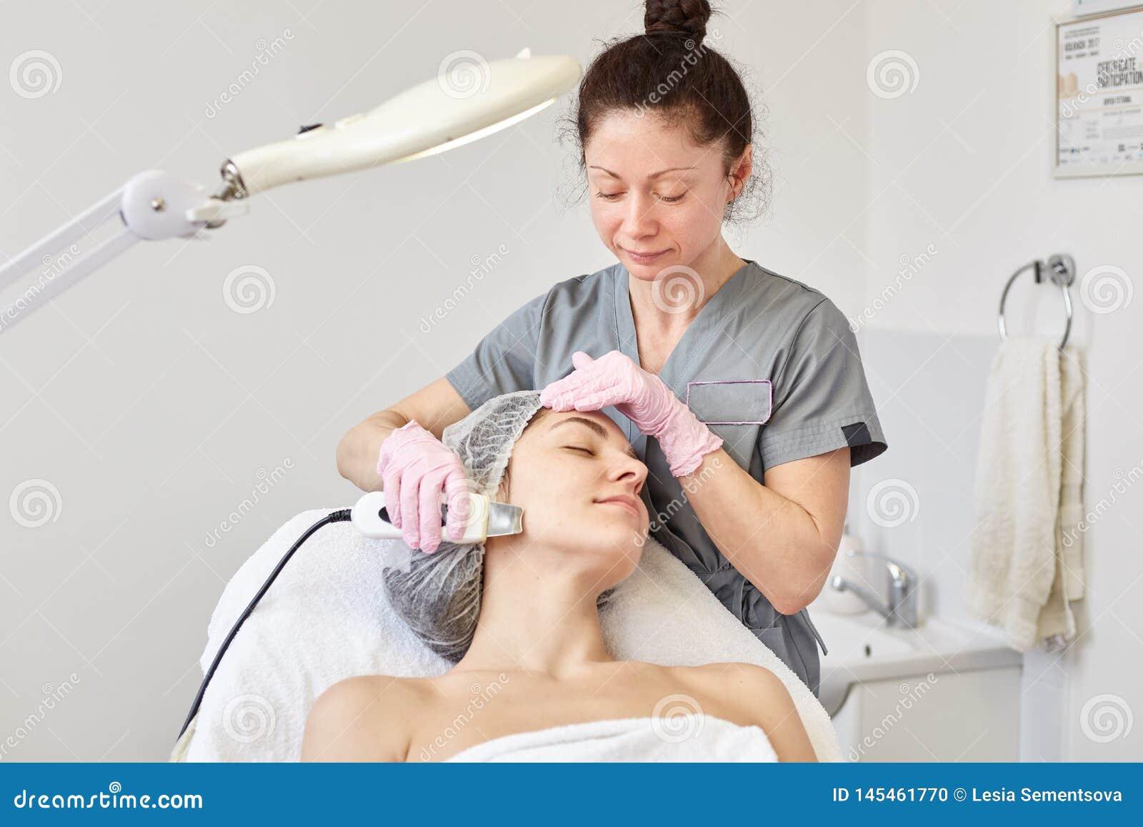 Het beeld van donkerbruine cosmetologist draagt grijze kleren die ultra sonische procedures die voor jonge dame doen op couh in d