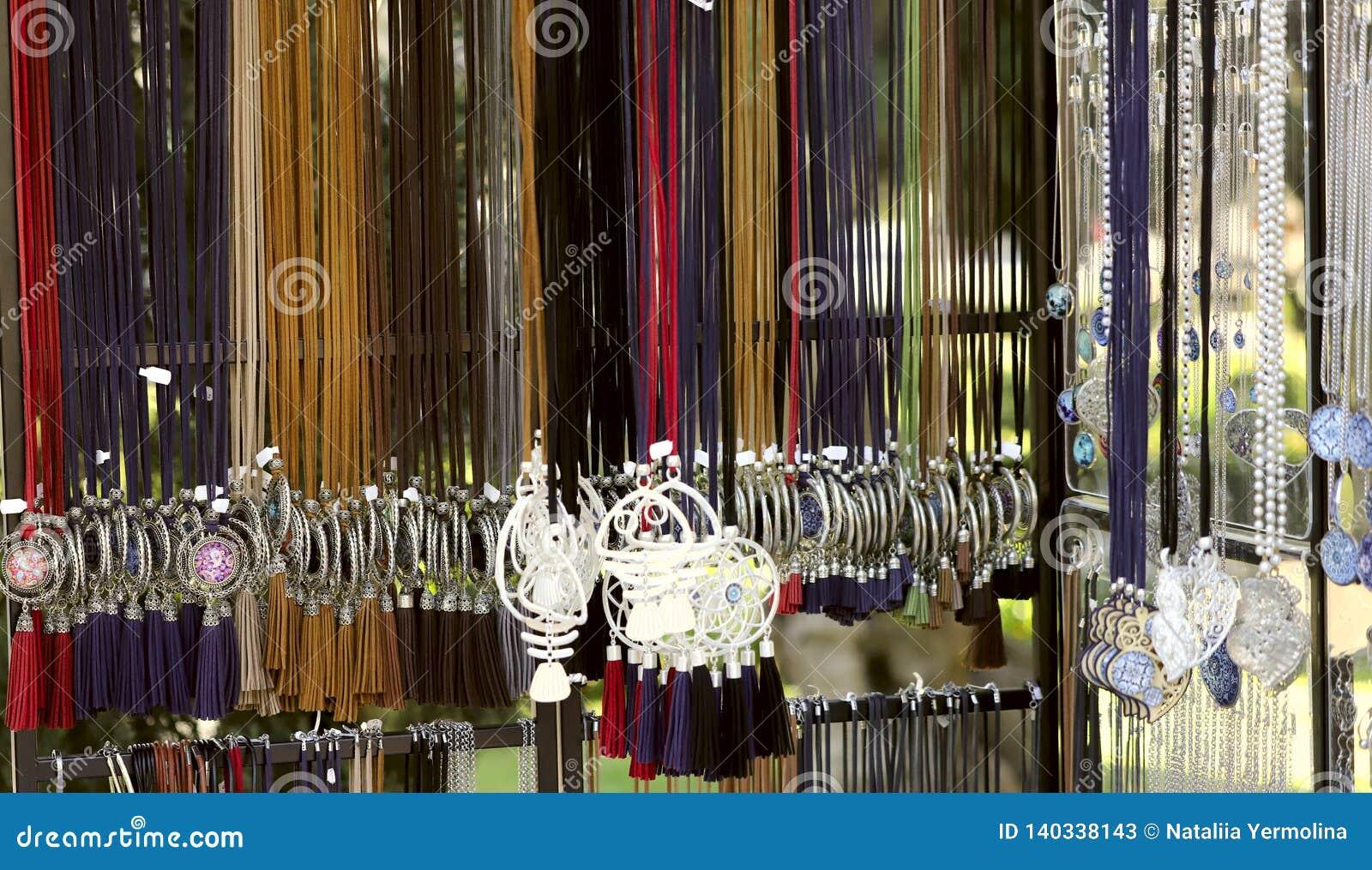 Het beeld van het hangen van de juwelen van vrouwen op gekleurd kant in de opslag Modieuze juwelen op de hals voor vrouwen