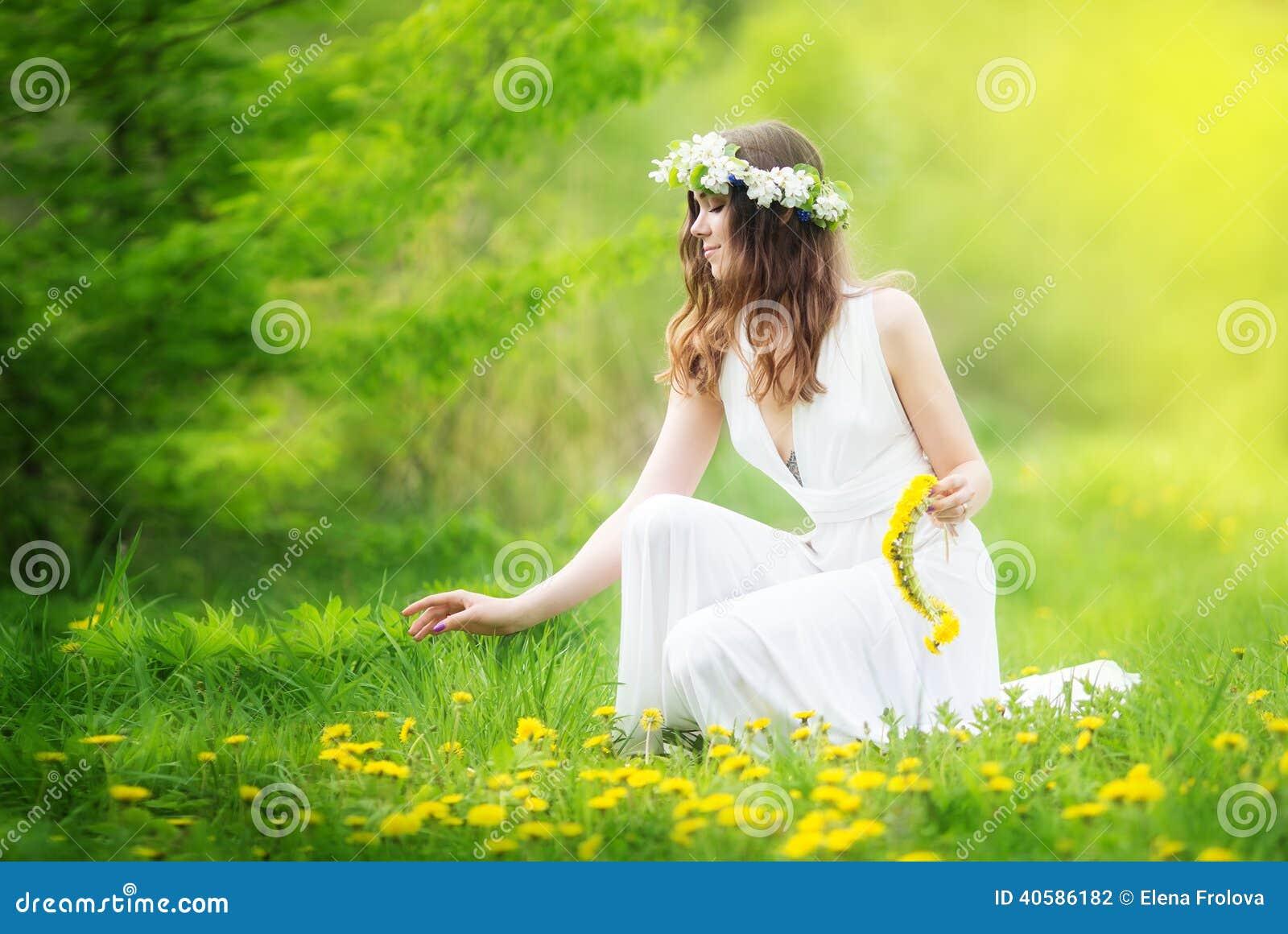 Het beeld van mooie vrouw in een witte kleding weeft slinger van dande