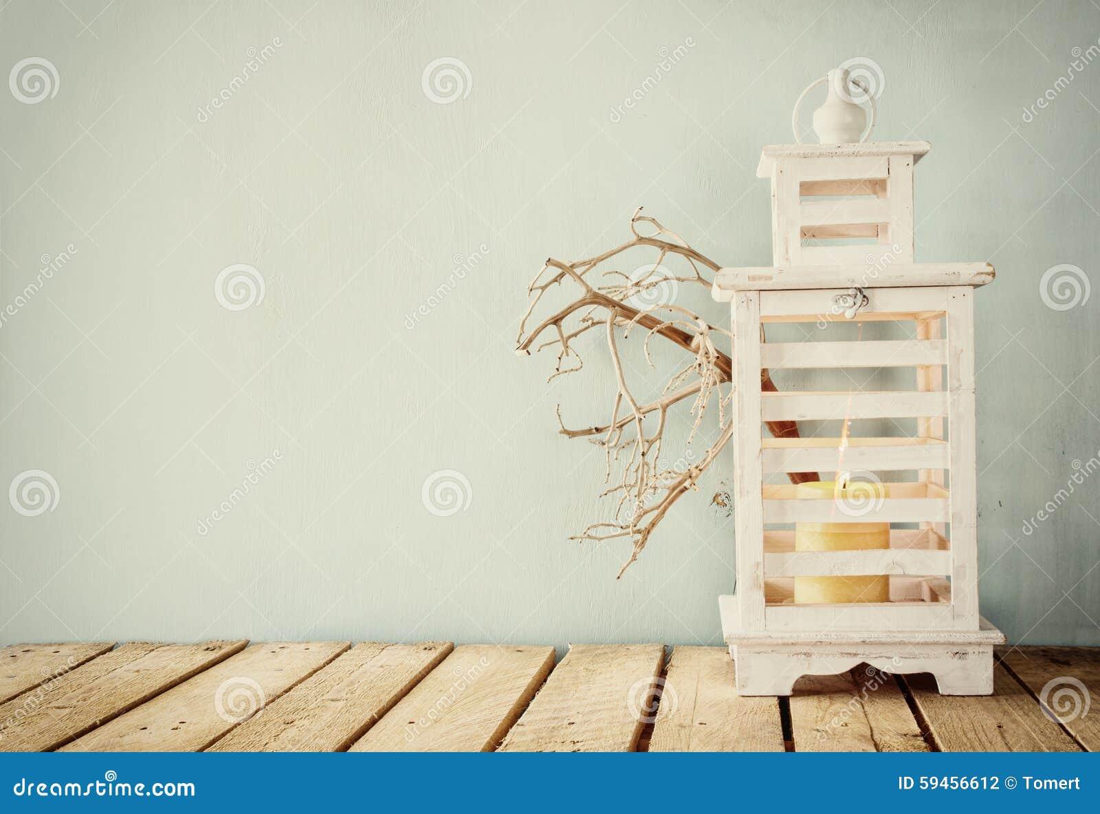 Het beeld van witte houten uitstekende lantaarn met het branden van kaars en boom vertakt zich op houten lijst retro gefiltreerd